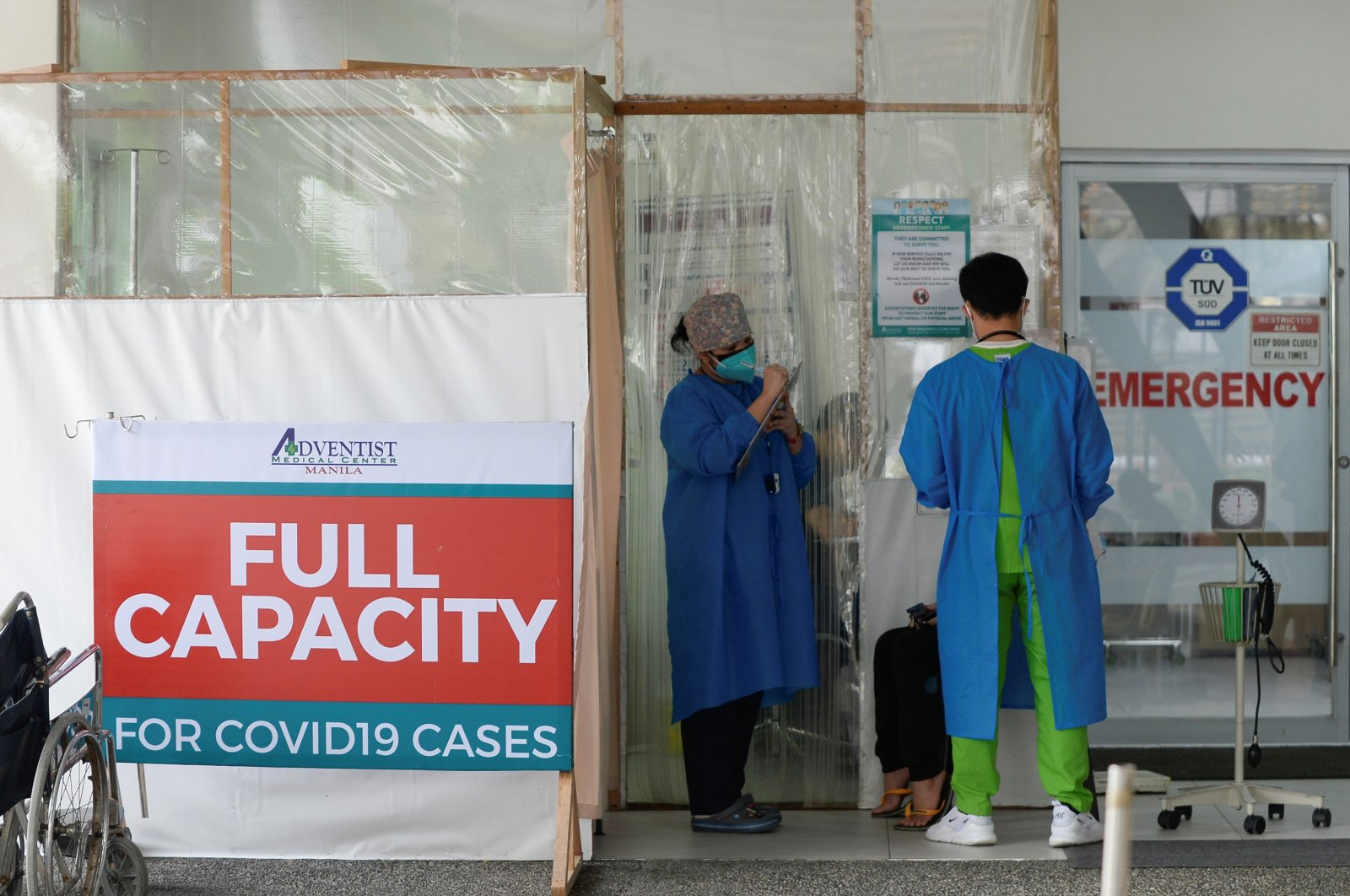 Health workers assess a patient outside the emergency room at the Adventist Medical Center, where a sign indicating that the hospital's coronavirus facility is at full capacity is displayed, in Pasay, the Philippines, April 9, 2021. (Reuters Photo)