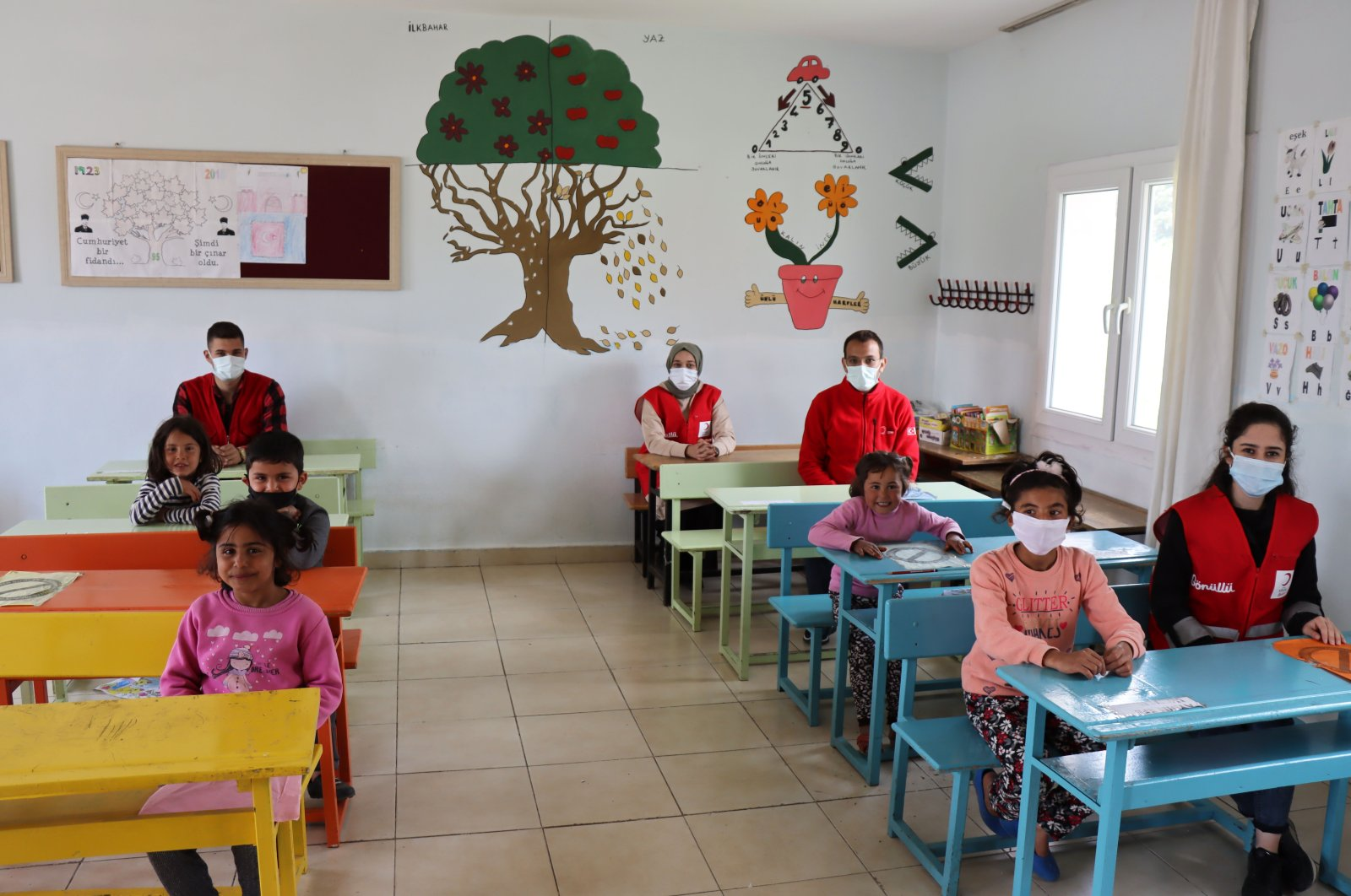Turkish Red Crescent volunteers and children sit in a classroom in a freshly-painted school in Polatlı village near the Syrian border, Kilis, April 9, 2021. (AA)