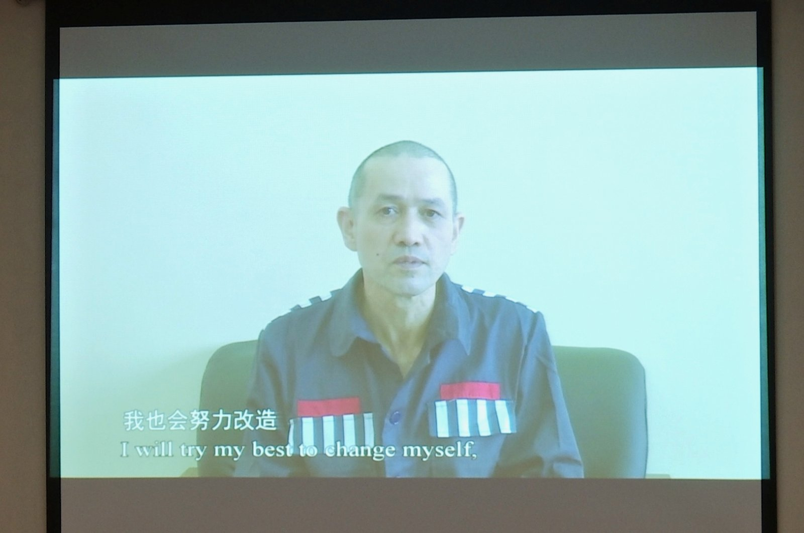 Erkin Tursun, a former TV producer who officials say is serving a 20-year sentence in Xinjiang, is seen speaking on a video shown at a news conference on Xinjiang-related issues, in Beijing, China April 9, 2021. (Reuters Photo)