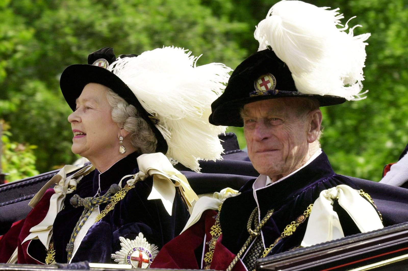 Britain's Queen Elizabeth II (L) and Prince Phillip, the Duke of Edinburgh, wearing their Order of the Garter robes, ride in an open-topped carriage to Windsor Castle following the Garter Ceremony, Windsor, U.K., June 18, 2001. (Reuters Photo)
