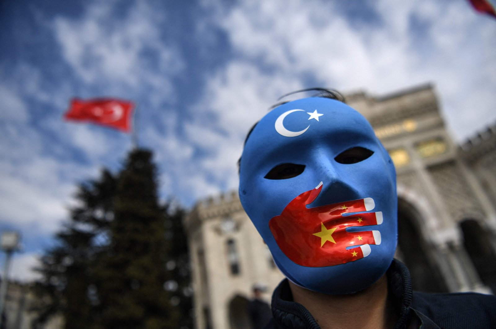 A demonstrator wearing a mask painted with the colors of the flag of East Turkestan takes part in a protest by supporters of the Uyghur minority, at Beyazıt square, Istanbul, Turkey, April 1, 2021. (AFP Photo)