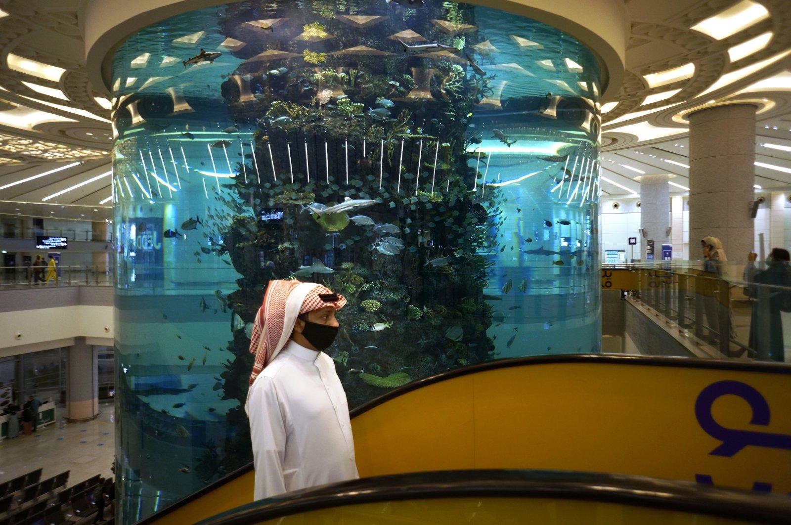A passenger walks in front of a giant aquarium at the King Abdulaziz International Airport in Jiddah, Saudi Arabia, April 9, 2021. (AP Photo)