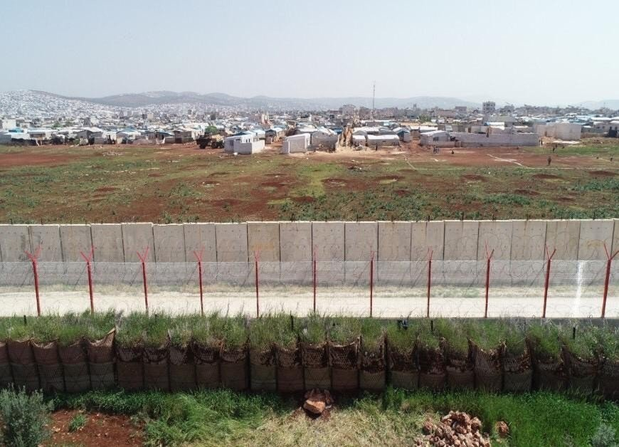 A section of the border running between Turkey and Syria is seen from the southern Turkish province of Hatay with the Syrian town of Atmeh in the background, April 10, 2021 (IHA Photo)