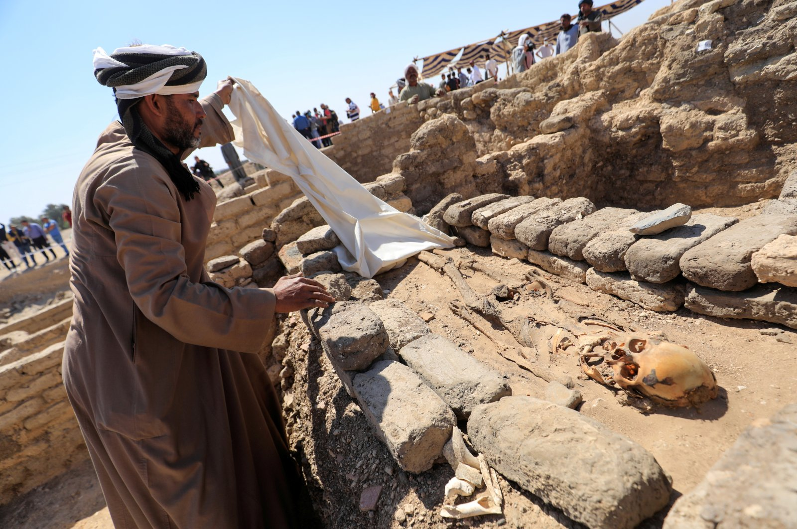 A man looks at skeletal human remains at the site of the 'Lost Golden City', which was recently discovered by archaeologists, in the West Bank of Luxor, upper Egypt, April 10, 2021. (Reuters Photo)