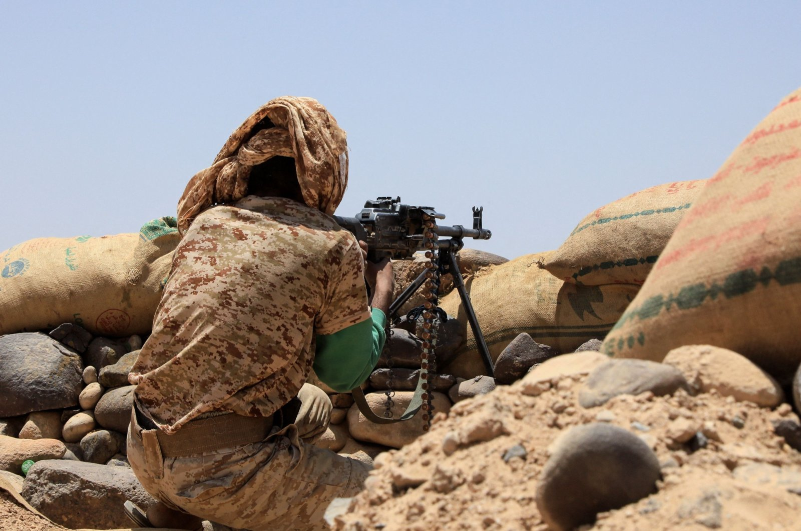 A fighter with forces loyal to Yemen's internationally-recognized government holds a position against Houthi rebels in Marib province, northwestern Yemen, April 6, 2021. (STR via AFP)