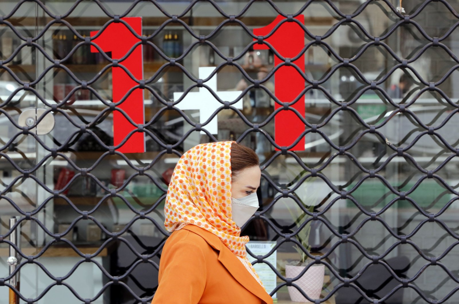 An Iranian woman wearing a face mask walks next to closed shops in a street in Tehran, Iran, April 10, 2021. (EPA Photo)