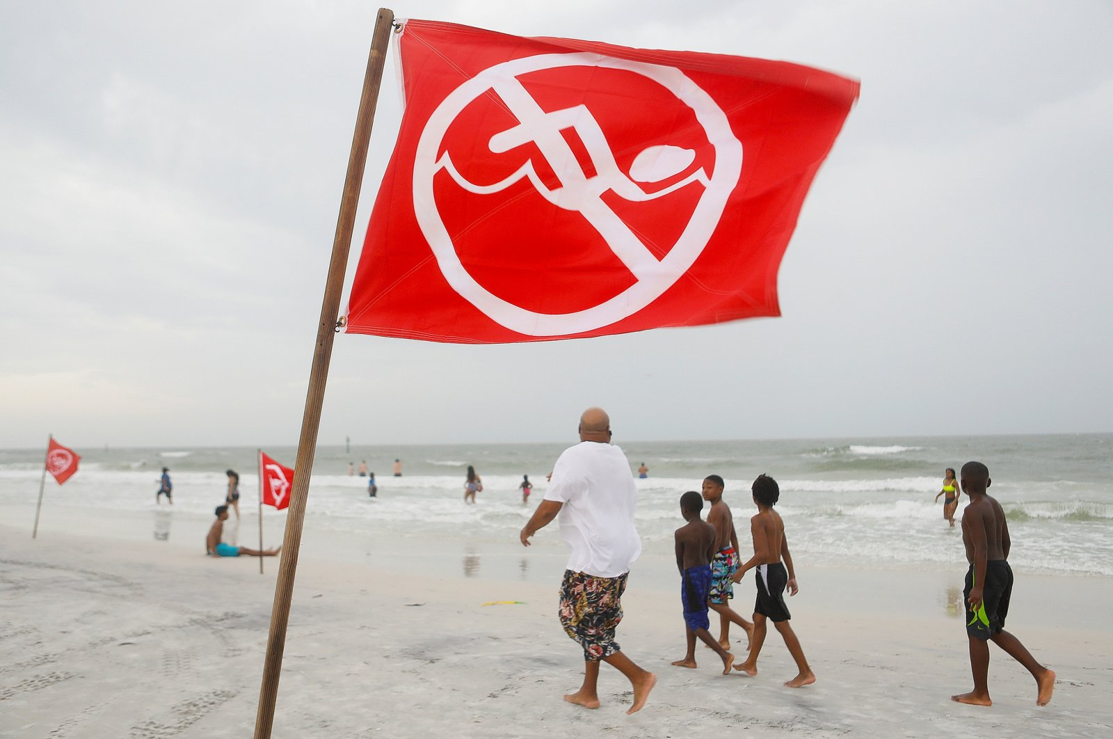 A strong current warning sign blows in the wind while beachgoers enjoy the Gulf of Mexico before a storm front approaches Clearwater Beach in Clearwater, Florida, U.S. March 18, 2021. (Reuters Photo)