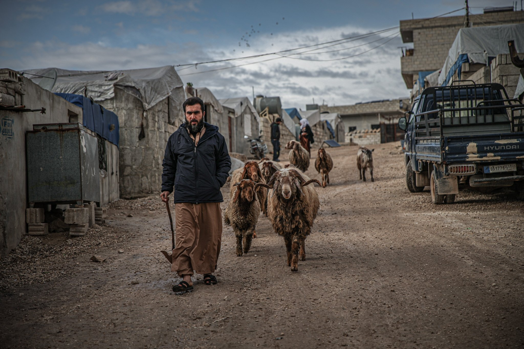 A refugee man is walking in a camp in northwestern Syria's Idlib with his goats, Idlib, Syria, April 11, 2021.