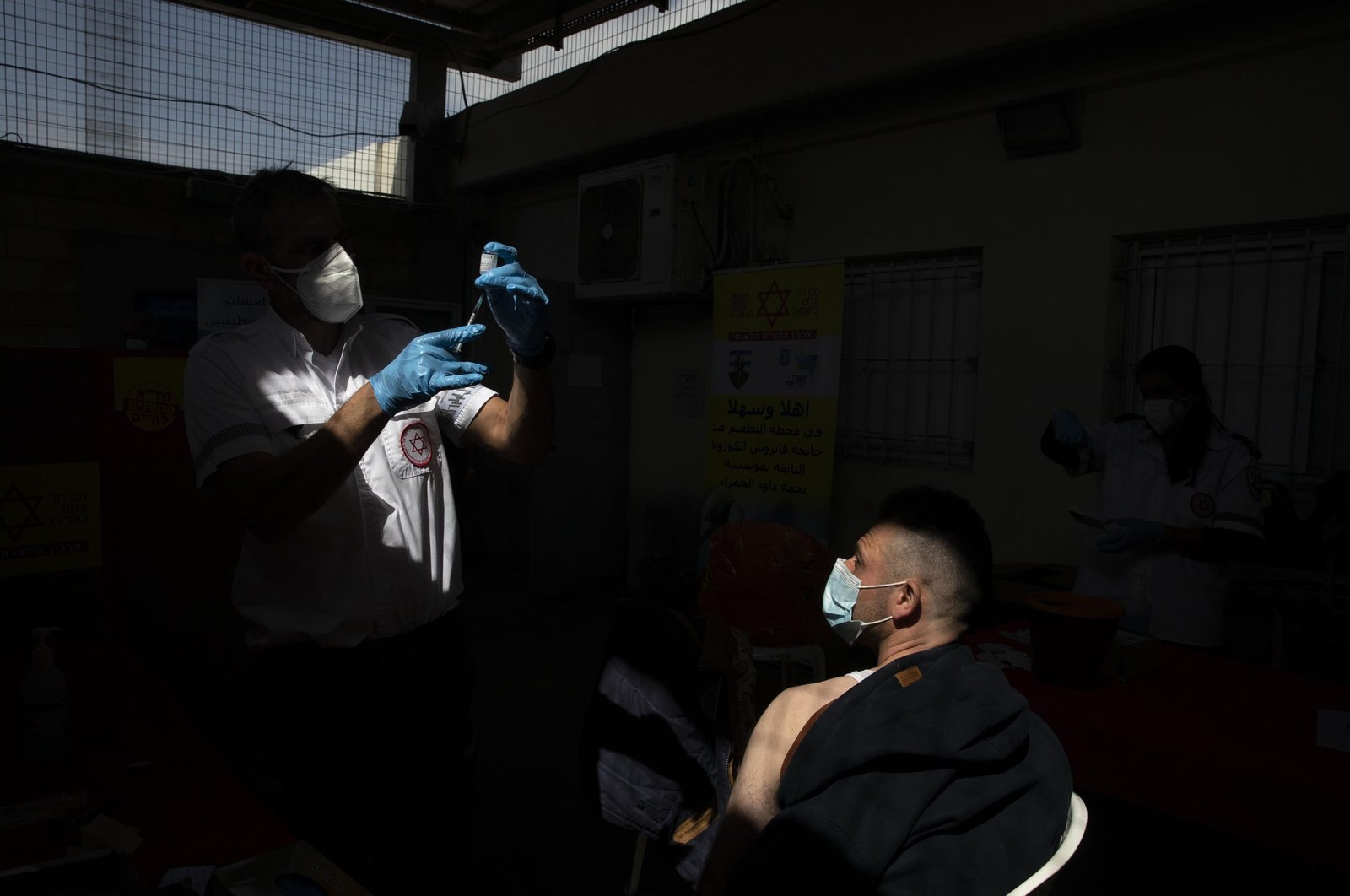 In this March 8, 2021, file photo, a Palestinian worker who works in Israel receives a Moderna COVID-19 vaccine at the Tarkumiya crossing between the West Bank and Israel. (AP Photo)