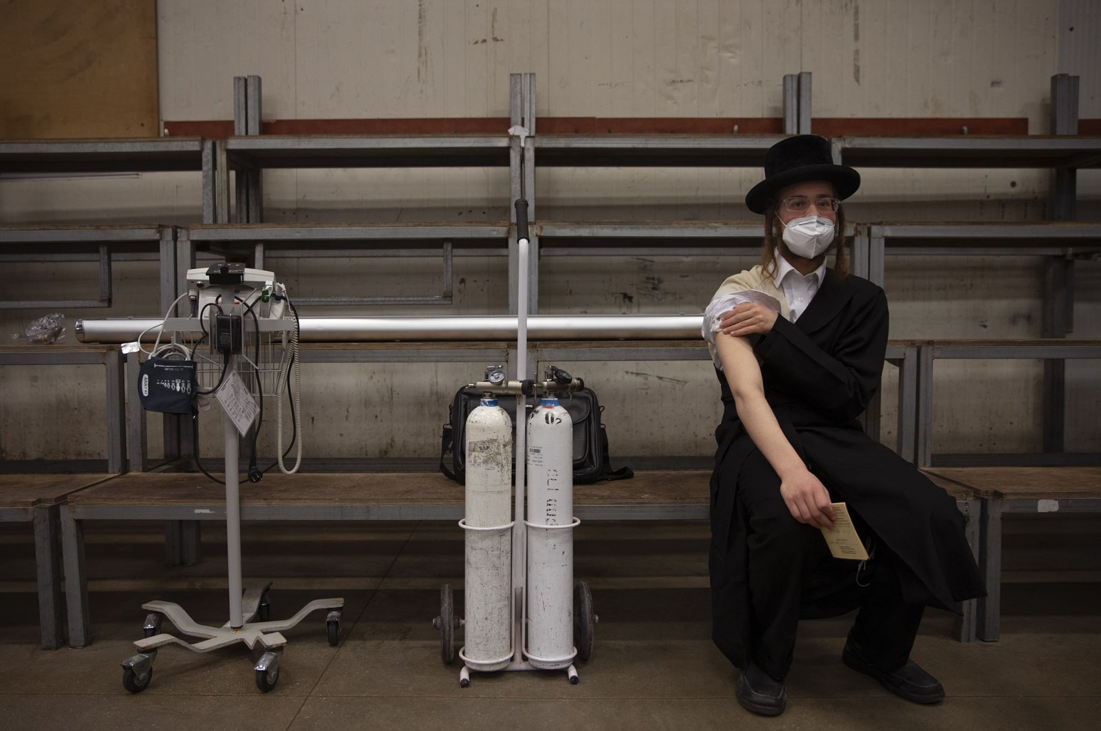 An ultra-Orthodox Jewish man rests after receiving his second dose of the Pfizer/BioNTech COVID-19 vaccine at a coronavirus vaccination center set up at a synagogue in Bnei Brak, Israel, Sunday, March. 7, 2021. (AP Photo)