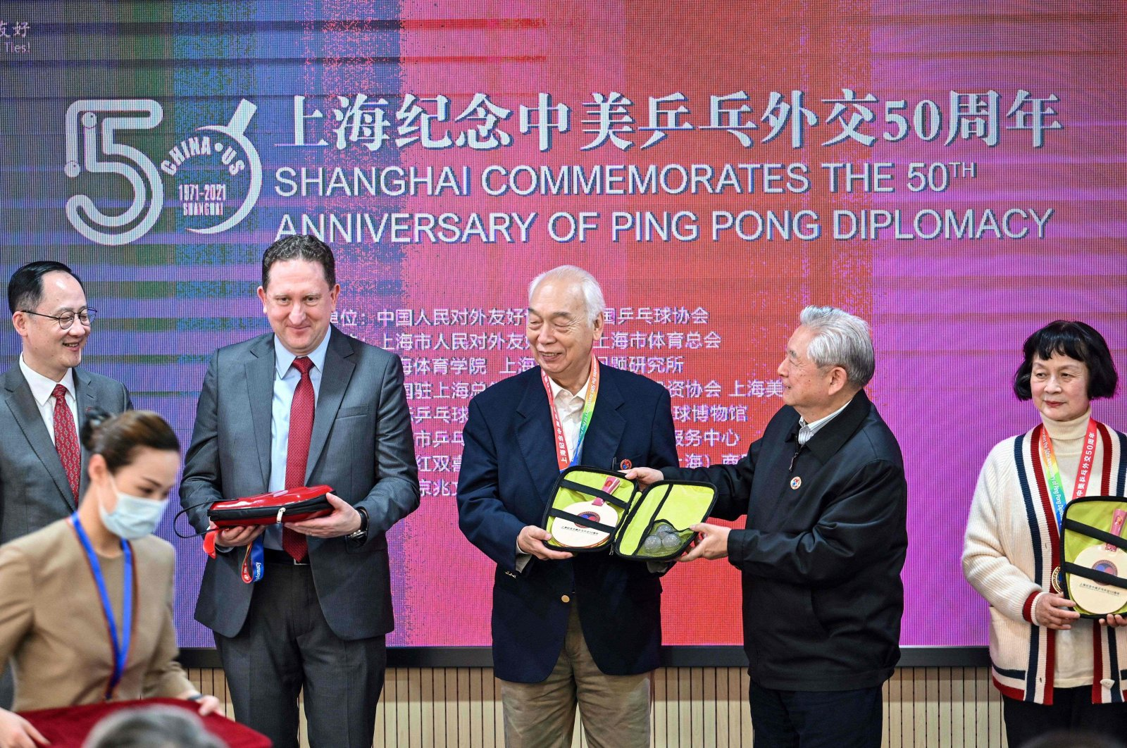 "U.S. Consul General in Shanghai James Heller (2nd L) with former Chinese table tennis players and ""ping-pong diplomacy"" participants Zhang Xielin (C) and Zheng Minzhi (R) receiving souvenirs during a ceremony to mark the 50th anniversary of the diplomatic event at the International Table Tennis Federation museum in Shanghai, April 10, 2021. (AFP Photo)"