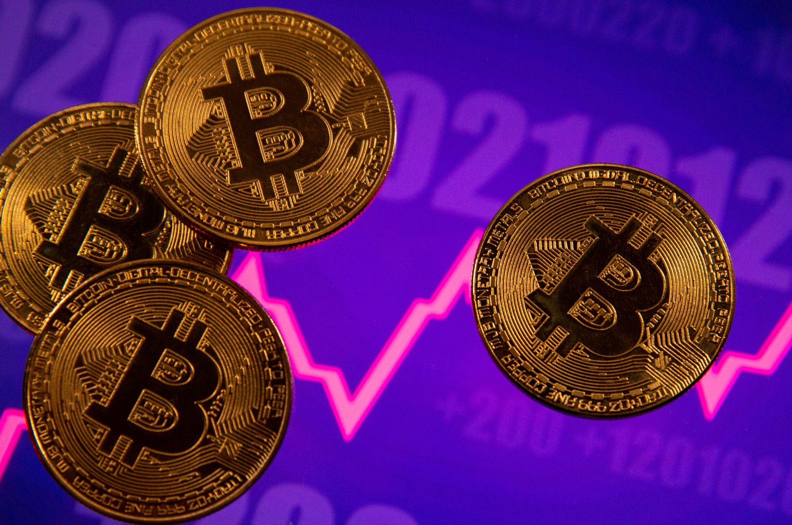 A representation of virtual currency Bitcoin in front of a stock graph in an illustration taken March 15, 2021. (Reuters Photo)