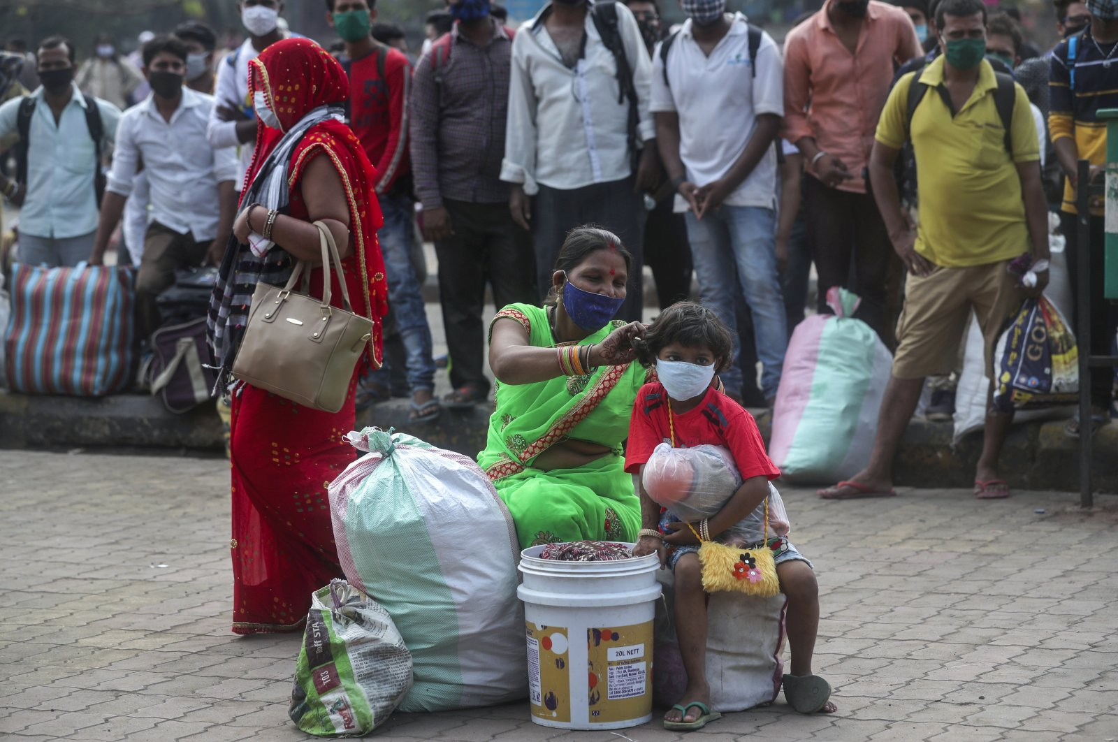 A woman adjusts the mask of her child as they wait for a train at Lokmanya Tilak Terminus in Mumbai, India, April 11, 2021. (AP Photo)