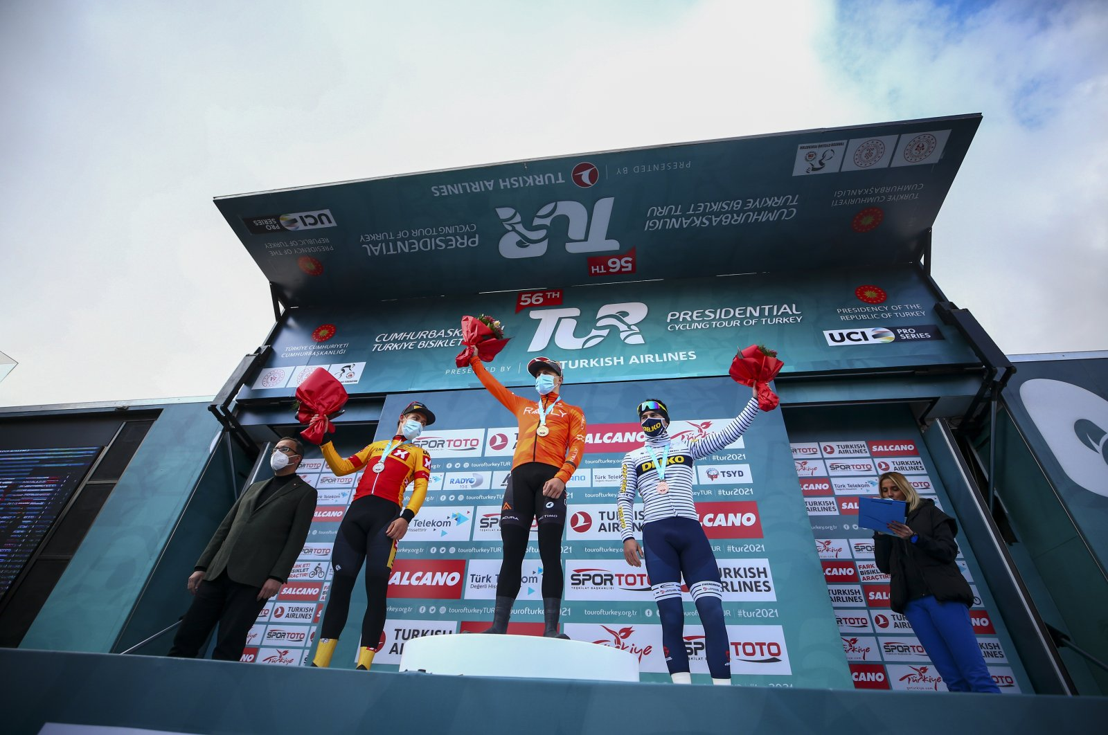 Winners of the bunch sprint event in the opening stage of the Tour of Turkey, Dutch rider Arvid de Kleijn of Rally Cycling (C), Norway's Kristoffer Halvorsen'e (2nd L) and France's Pierre Barbier (R) are accompanied by Turkey's Sports Minister Mehmet Muharrem Kasapoğlu, Konya, central Turkey, Sunday, April 11, 2021.