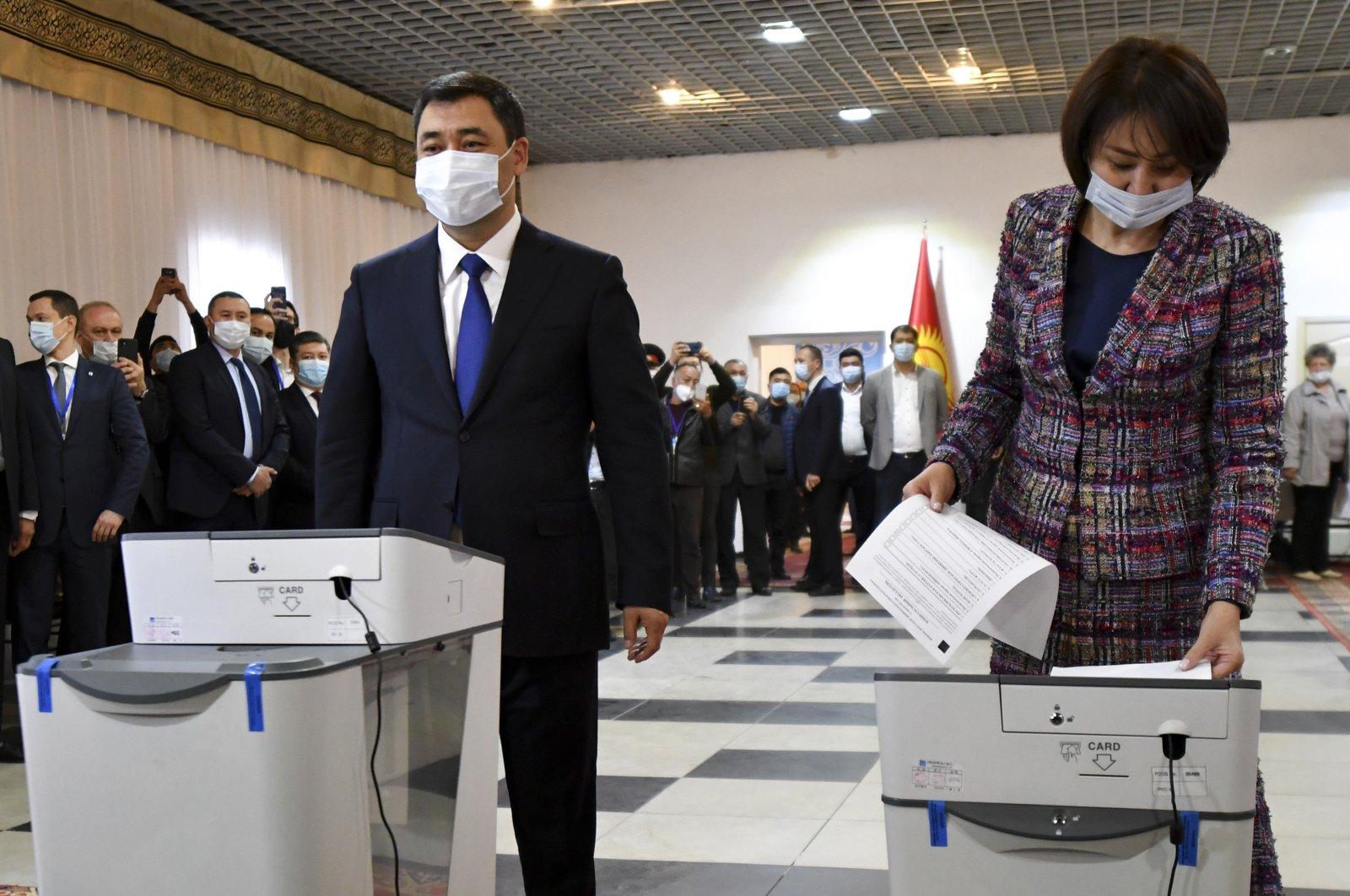 Kyrgyzstan's President Sadyr Japarov and his wife Aigul Asanbaeva cast their ballots at a polling station during the referendum in Bishkek, Kyrgyzstan, April 11, 2021. (AP Photo)