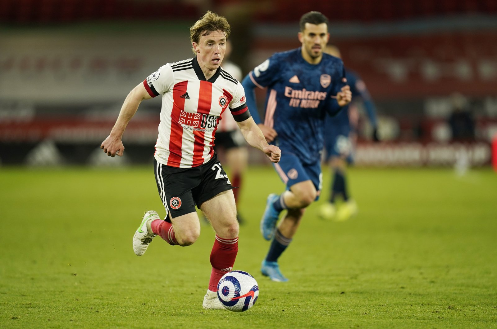Sheffield United's Ben Osborn, left, controls the ball during the English Premier League soccer match between Sheffield United and Arsenal at the Bramall Lane stadium in Sheffield, England, Sunday, April 11, 2021. (AP Photo)