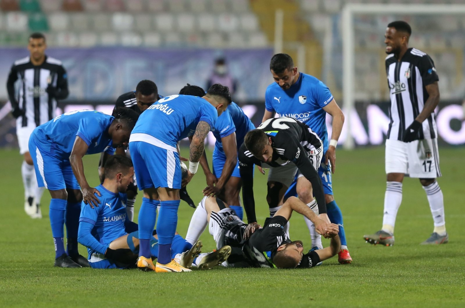 Beşiktaş and Erzurumspor players gather round forward Cenk Tosun as he lies in pain on the ground due to a knee injury, Erzurum, eastern Turkey, April 12, 2021. (AA Photo)