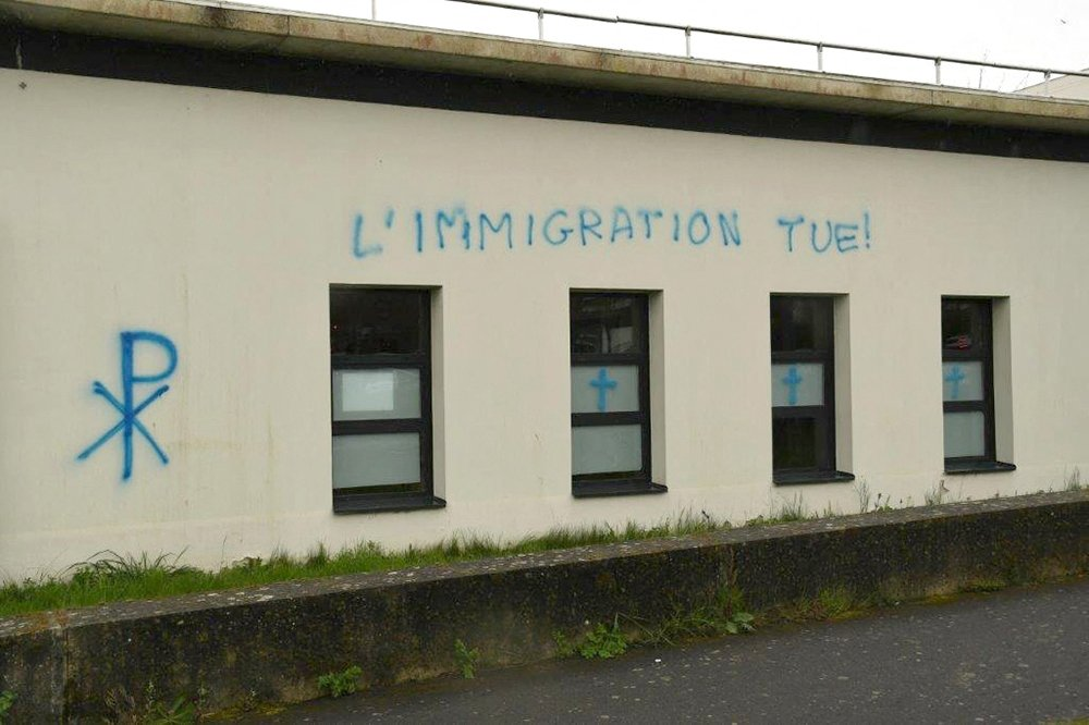 """This handout picture released by the French Ministry of Justice shows graffiti tags that read, """"Immigration kills,"""" sprayed on the walls of the Avicenna mosque and Islamic cultural center in Rennes, western France, April 11, 2021. (AFP Photo)"""