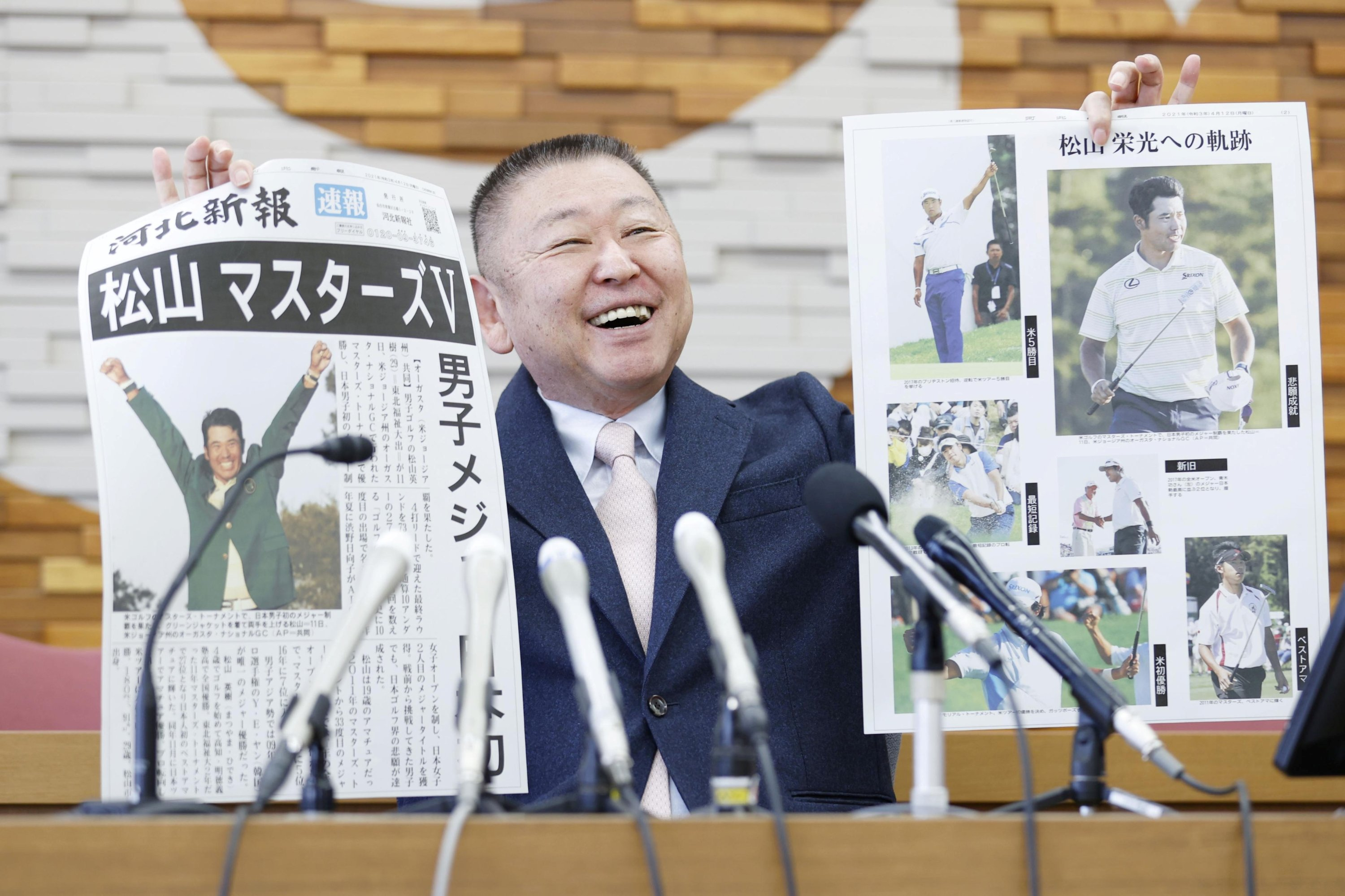 Yasuhiko Abe, who coached golfer Hideki Matsuyama during his Tohoku Fukushi University years, holds special editions of newspapers featuring Matsuyama's Masters victory as he speaks at a press conference in Sendai, Japan, April 12, 2021. (Reuters Photo)