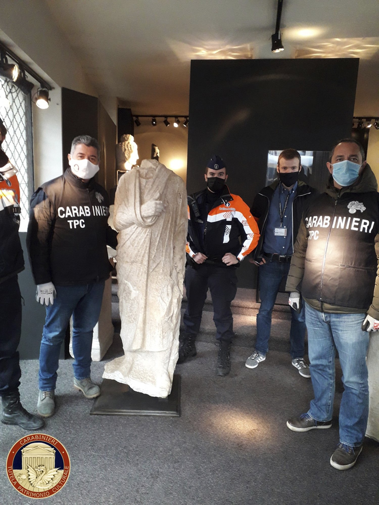 Carabinieri (Italian paramilitary police) officers of the art squad's archaeological unit pose with the headless Roman statue wearing a draped toga in Brussels, Belgium, Feb. 3, 2021. (Carabinieri via AP)