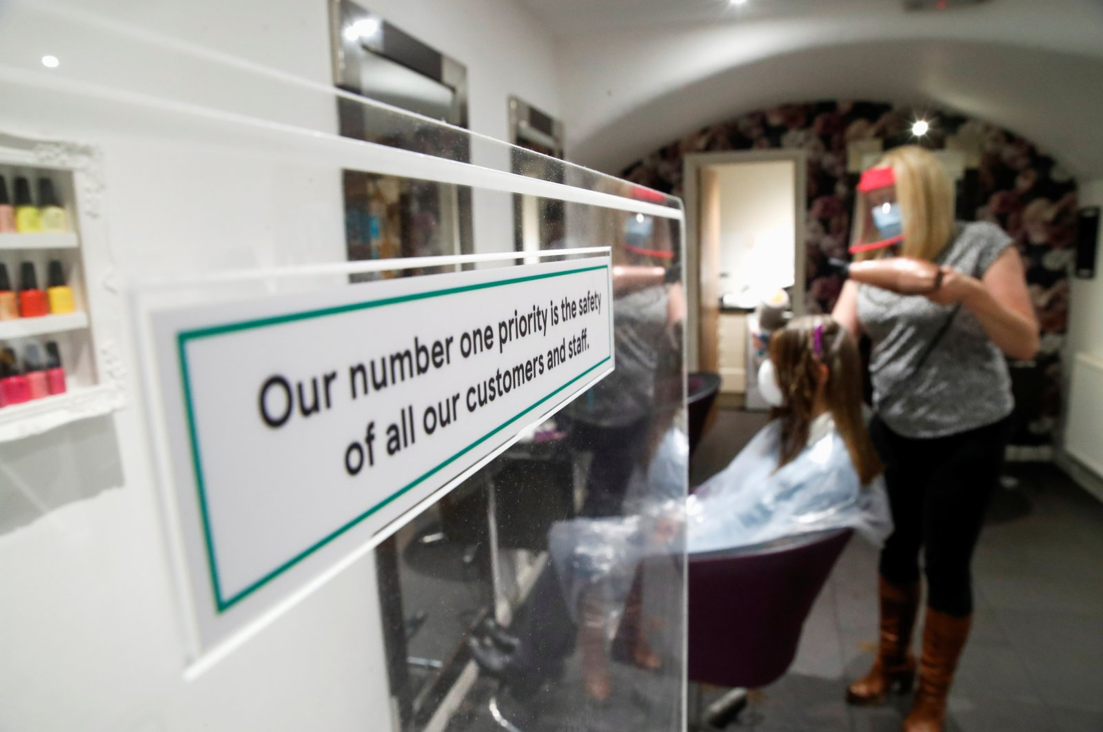 The owner of Hair & Beauty Gallery blow-dries a customer's hair as non-essential businesses reopen as COVID-19 lockdown restrictions begin to ease in Warwick, Britain, April 12, 2021. (Reuters Photo)