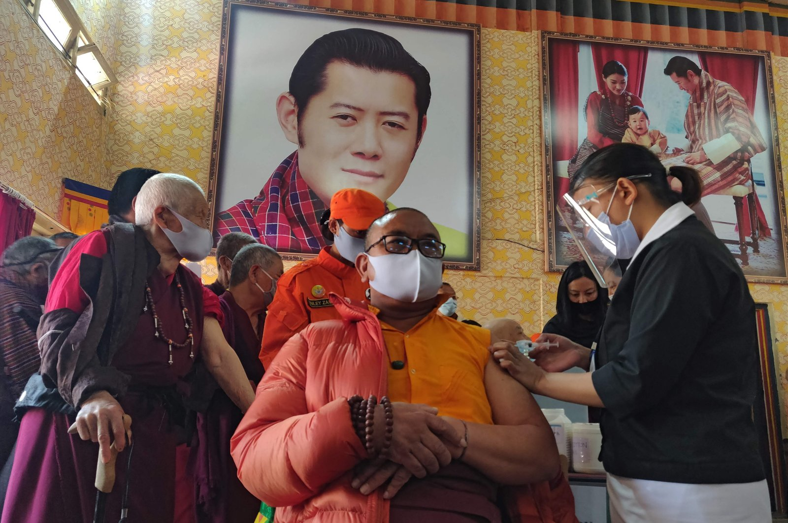 A health worker gives a dose of a COVID-19 vaccine to a Buddhist monk sitting in front of a portrait of Bhutan's King Jigme Khesar Namgyel Wangchuck, at Lungtenzampa Middle Secondary School in Thimphu, Bhutan, March 27, 2021. (AFP Photo)