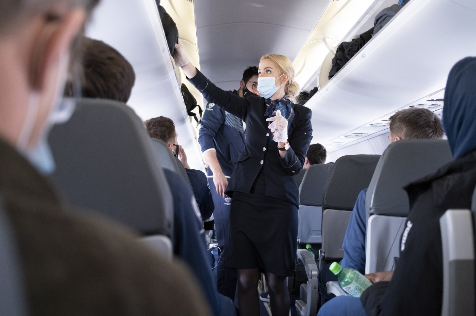 A flight attendant wearing a protective face mask speaks with passengers in a Bulgaria Air flight to Sofia, Bulgaria during the coronavirus (COVID-19) outbreak, Zurich, Switzerland, March 26, 2021. (EPA Photo)