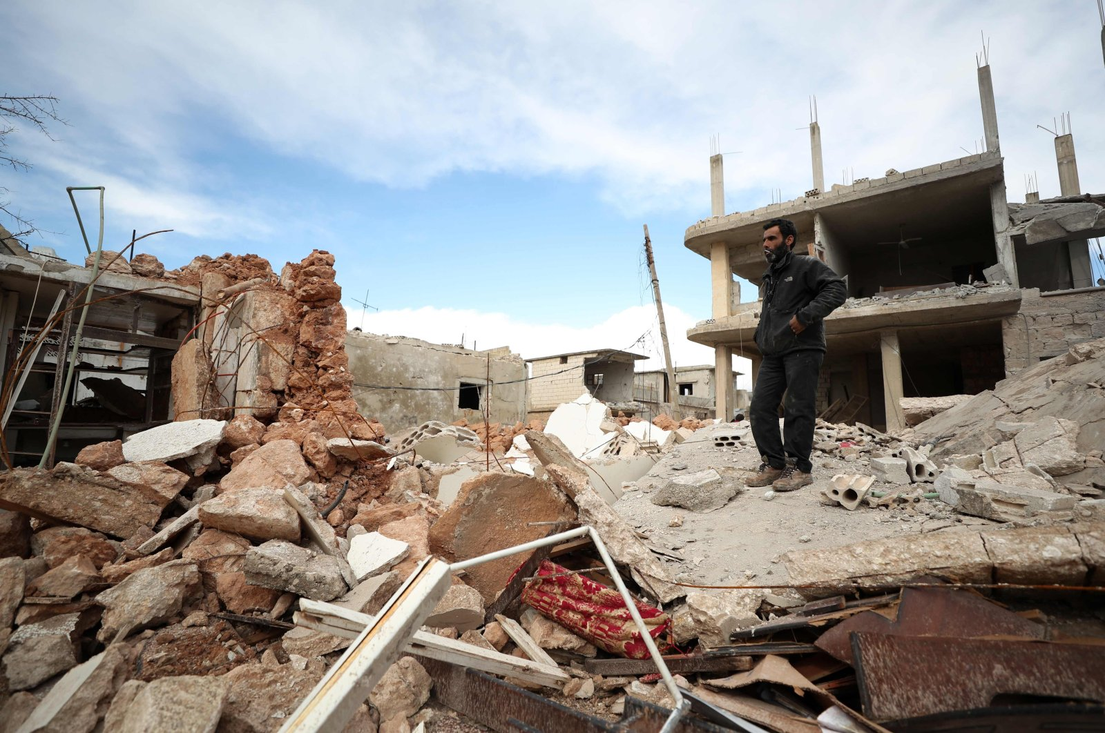 A man stands amid the rubble of a destroyed building in the town of Saraqib, in the northwestern province of Idlib, Syria, Jan. 31, 2020. (AFP Photo)
