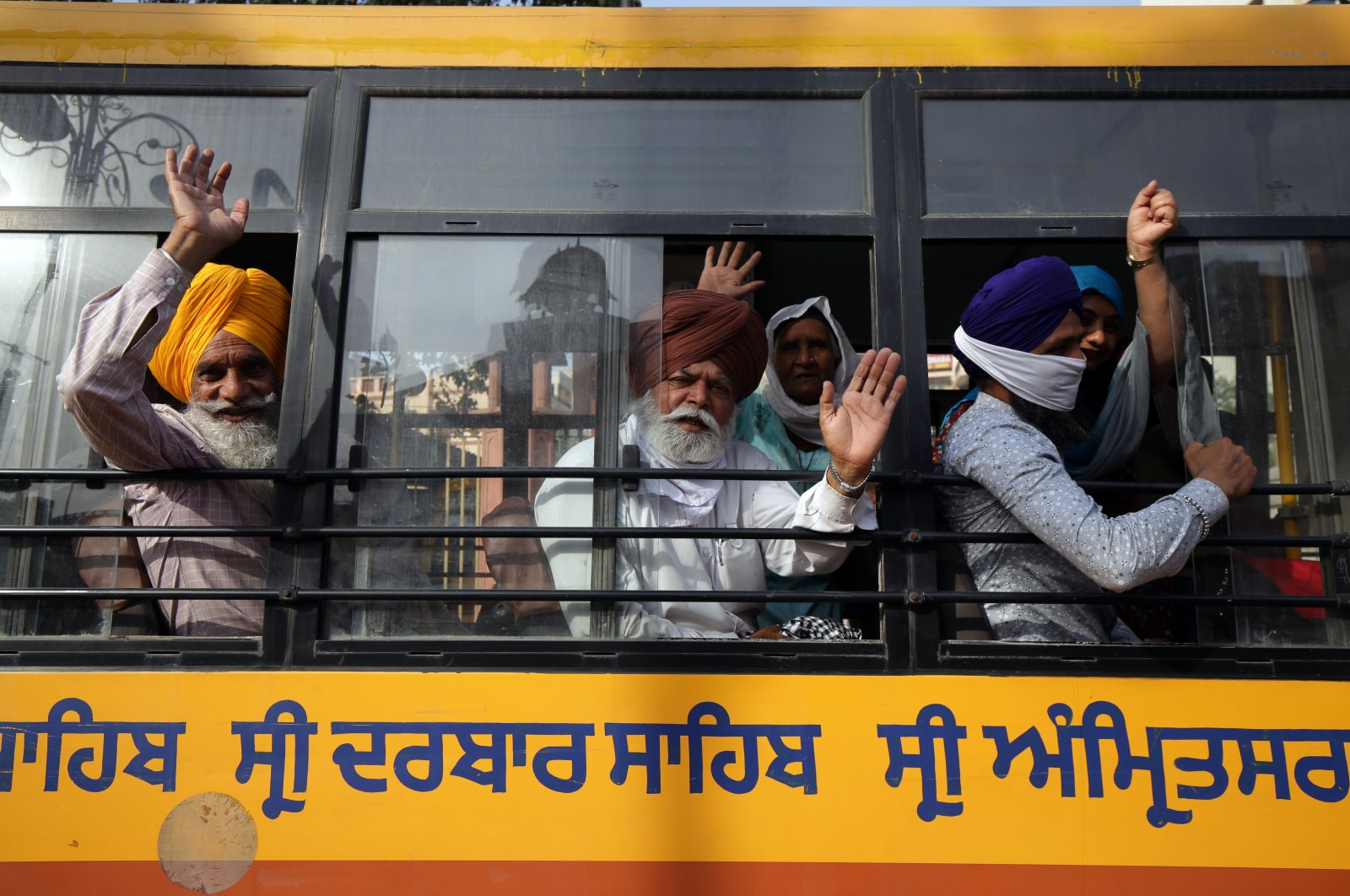 Sikh devotees wave from inside a bus as they leave for the border to cross into Pakistan to take part in the Baisakhi festival religious festivities, in Amritsar, India, 12 April, 2021. (EPA Photo)