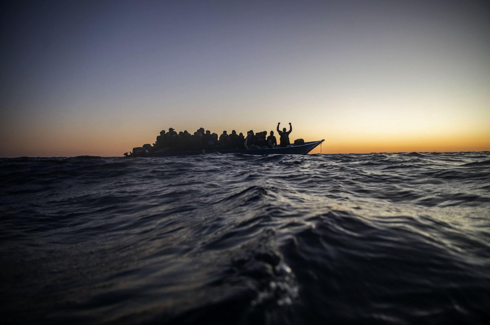 Migrants and refugees from different African nationalities wait for assistance on an overcrowded wooden boat in the Mediterranean Sea, international waters, at 122 miles (196 kilometers) off the Libyan coast, Feb. 12, 2021. (AP Photo)