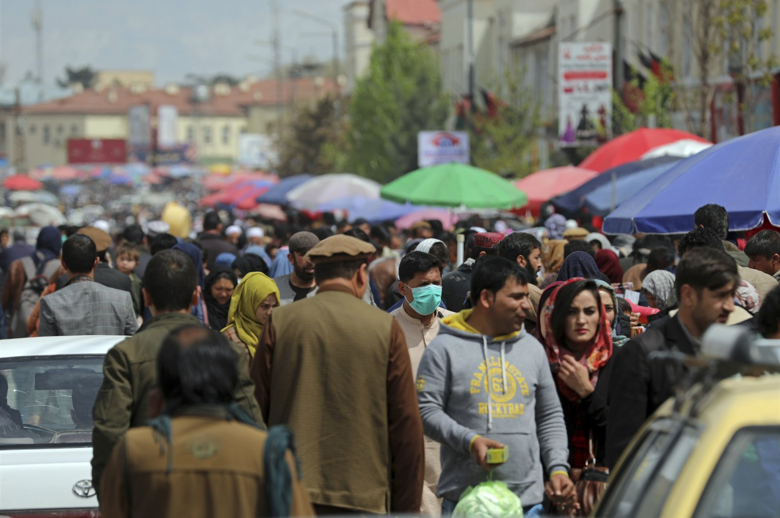 A man wearing a protective face mask to help curb the spread of the coronavirus walks among crowds in a street market in Kabul, Afghanistan, April 7, 2021. (AP Photo)