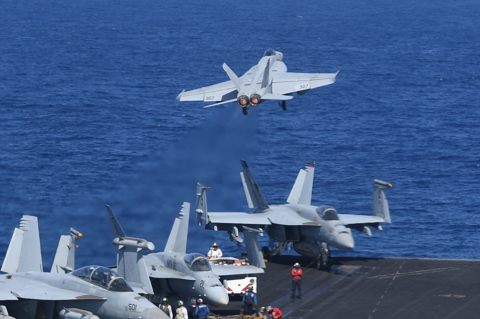 A US FA-18 hornet fighter jet flies past fighter jets and an E-2C Hawkeyes during a routine training exercise aboard U.S. aircraft carrier Theodore Roosevelt in the South China Sea on April 10, 2018. (AFP Photo)