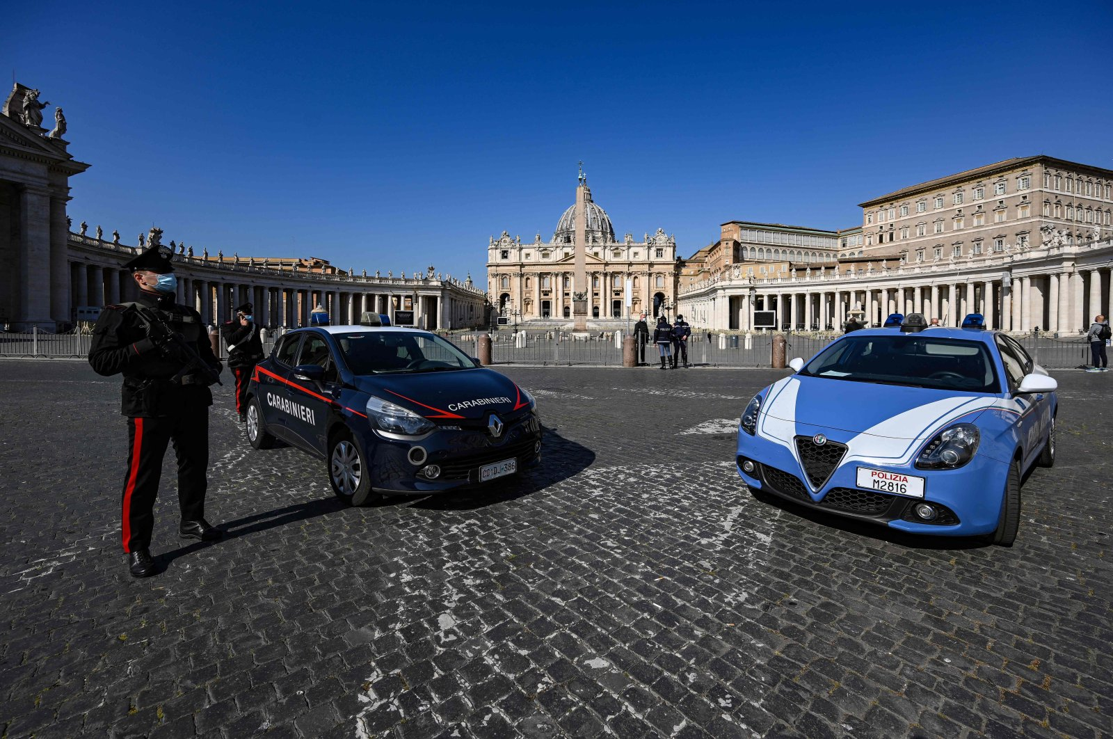 An Italian Carabinieri Police officer (L) stands guard at the limit between Italy in Rome and Saint Peter's Square in The Vatican, with Saint Peter's Basilica in the background, in The Vatican, March 28, 2021. (AFP Photo)