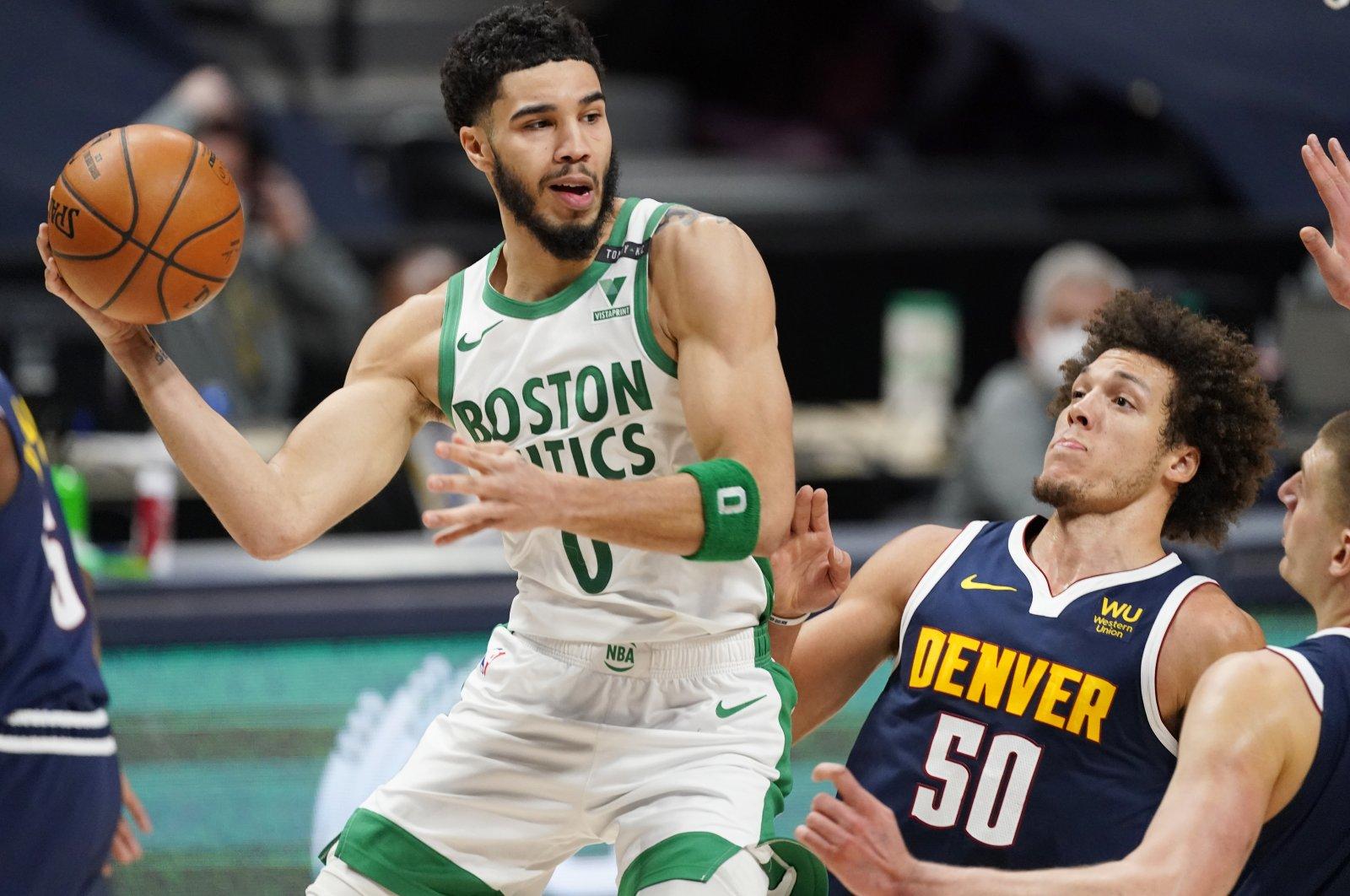 Boston Celtics forward Jayson Tatum (L) passes the ball as Denver Nuggets forward Aaron Gordon (C) and center Nikola Jokic defend during an NBA basketball game, Denver, U.S., April 11, 2021. (AP Photo)