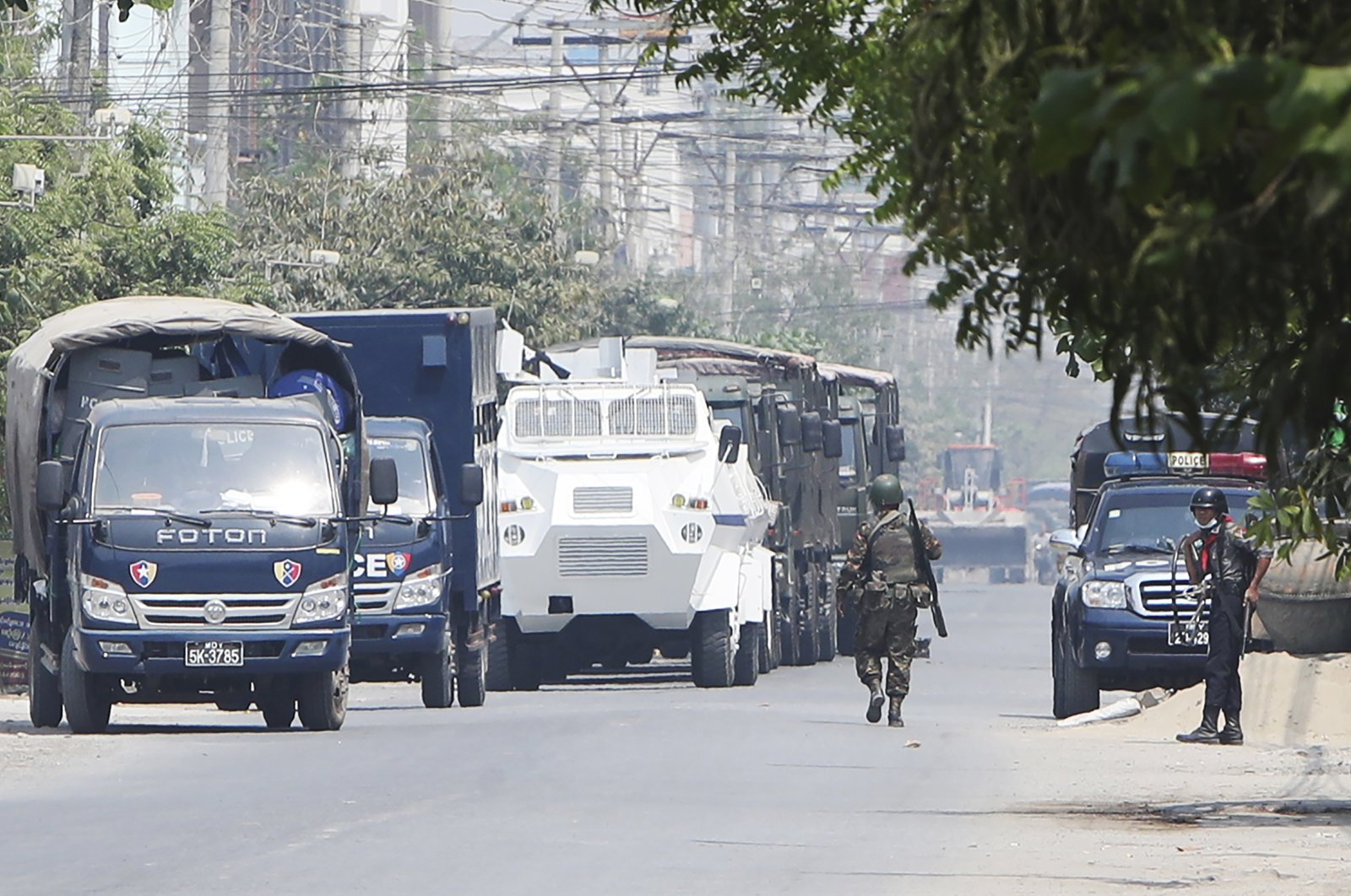 A soldier walks along a row of vehicles of security forces parked on a road in Mandalay, Myanmar, March 19, 2021. (AP Photos)