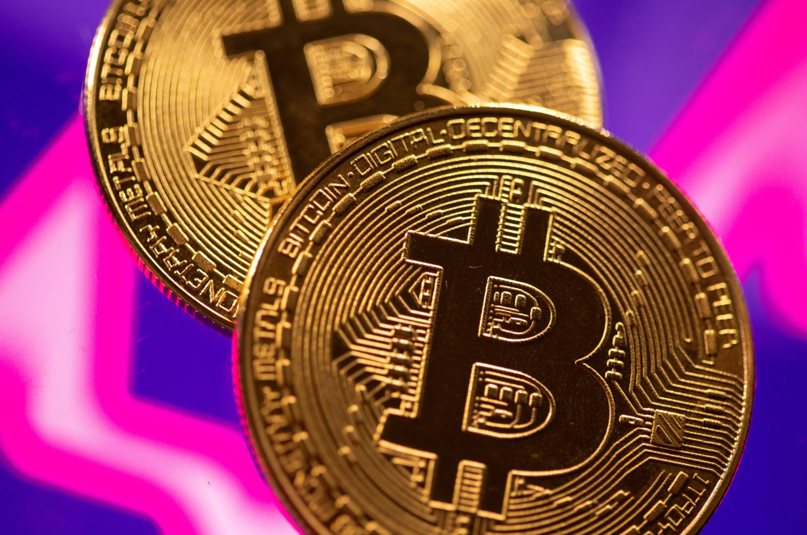 A representation of virtual currency Bitcoin is seen in front of a stock graph in this illustration taken March 15, 2021. (Reuters Photo)
