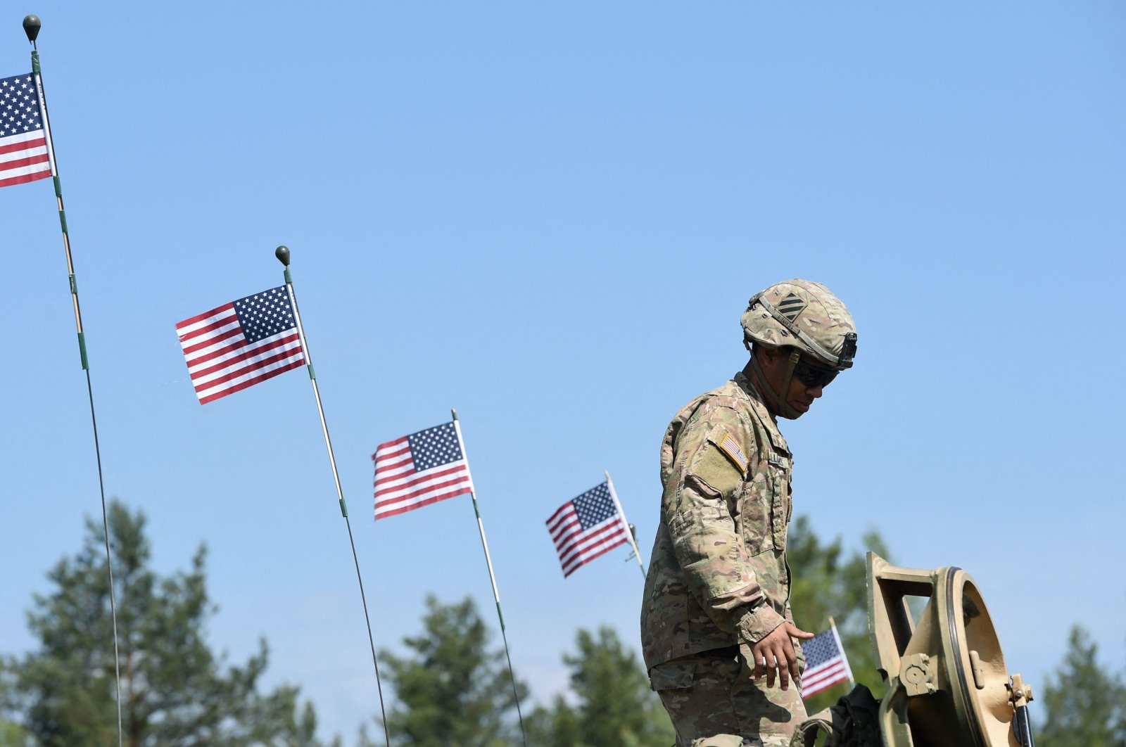 An American soldier stands next to U.S. flags at the military training area in Grafenwohr, near Eschenbach, southern Germany, May 11, 2016. (AFP Photo)