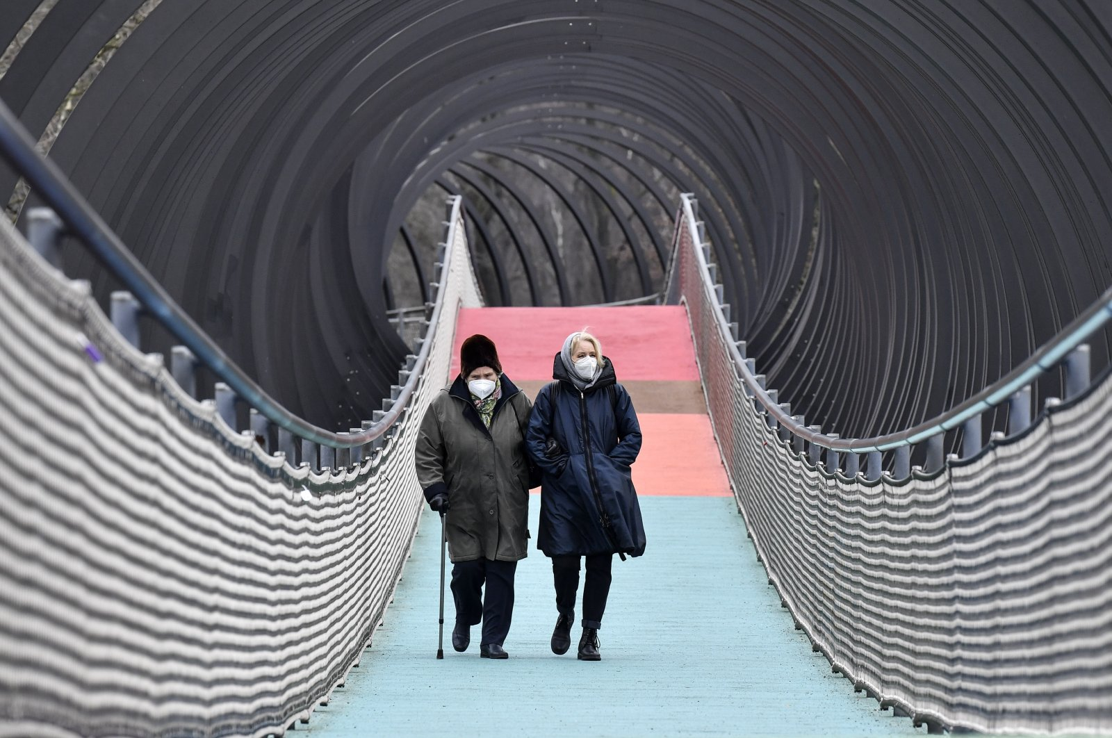 People wear protective face masks as they walk over a bridge during the lockdown in Oberhausen, Germany, on Monday, Jan. 11, 2021. (AP Photo)