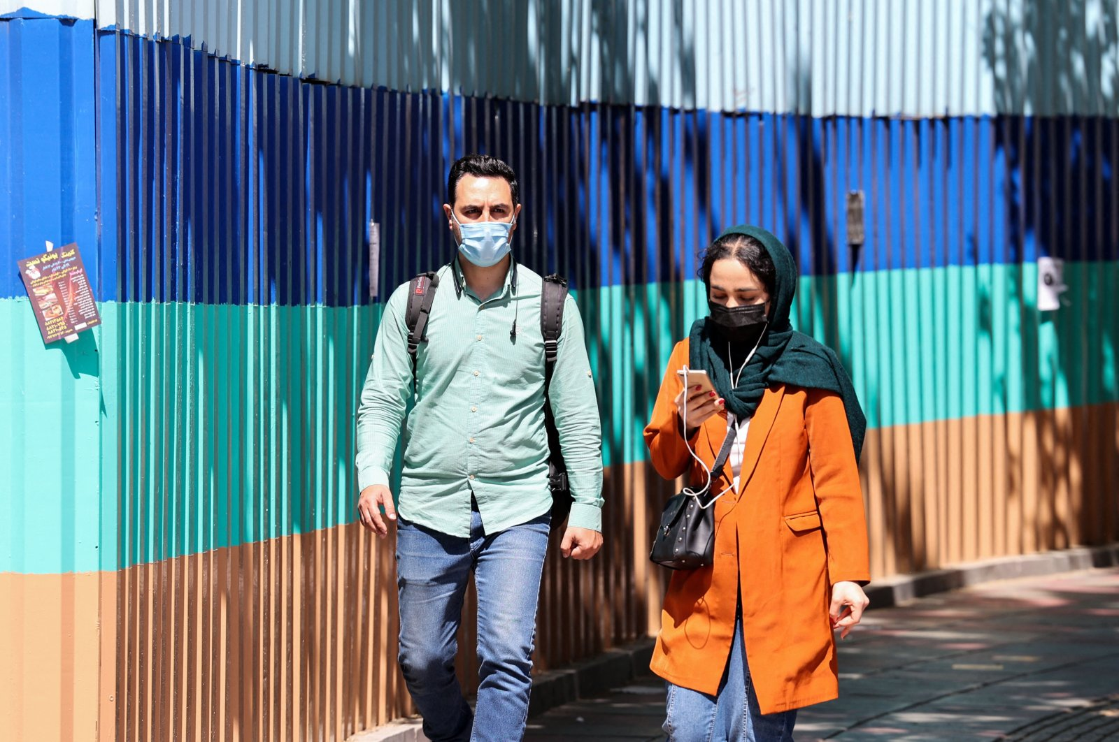 Iranians wearing protective masks walk on a sidewalk, following the tightening of restrictions to curb the surge of COVID-19 cases, in the capital Tehran, Iran, April 12, 2021. (AFP Photo)