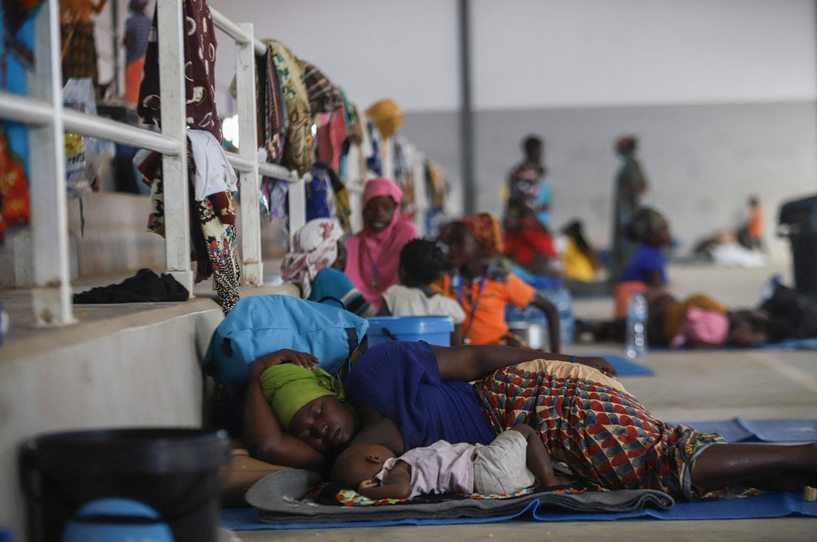 A woman rests with her baby on the ground at the Pemba Sports center that is now a shelter in Pemba, Mozambique, April 2, 2021. (AFP Photo)