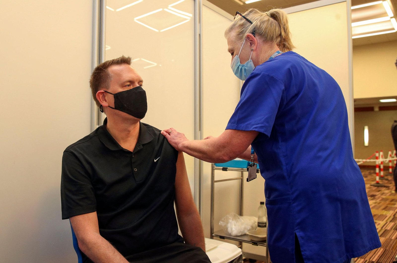 Martin Pluves receives an injection of the Moderna COVID-19 vaccine administered by nurse Paula Bartlett, at the Madejski Stadium in Reading, west of London on April 13, 2021. (AFP Photo)