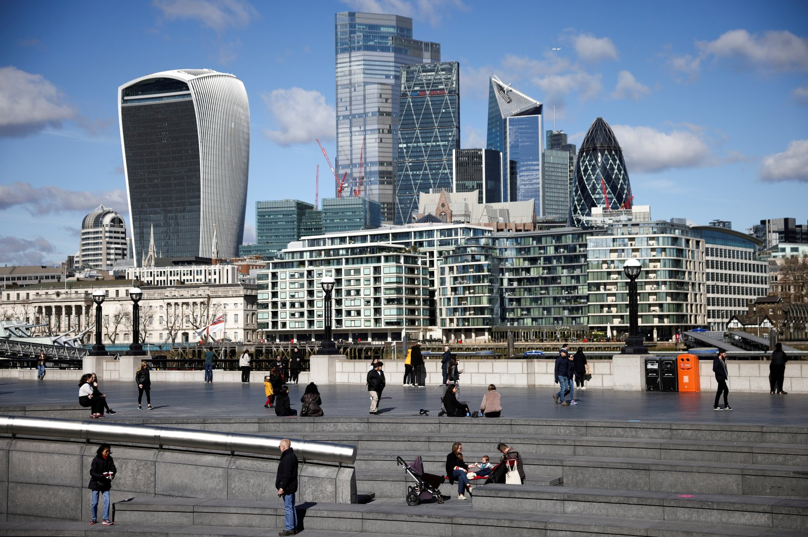 People walk along the south side of the River Thames with the City of London financial district in the background, amid the coronavirus disease (COVID-19) outbreak in London, Britain, March 19, 2021. (Reuters Photo)