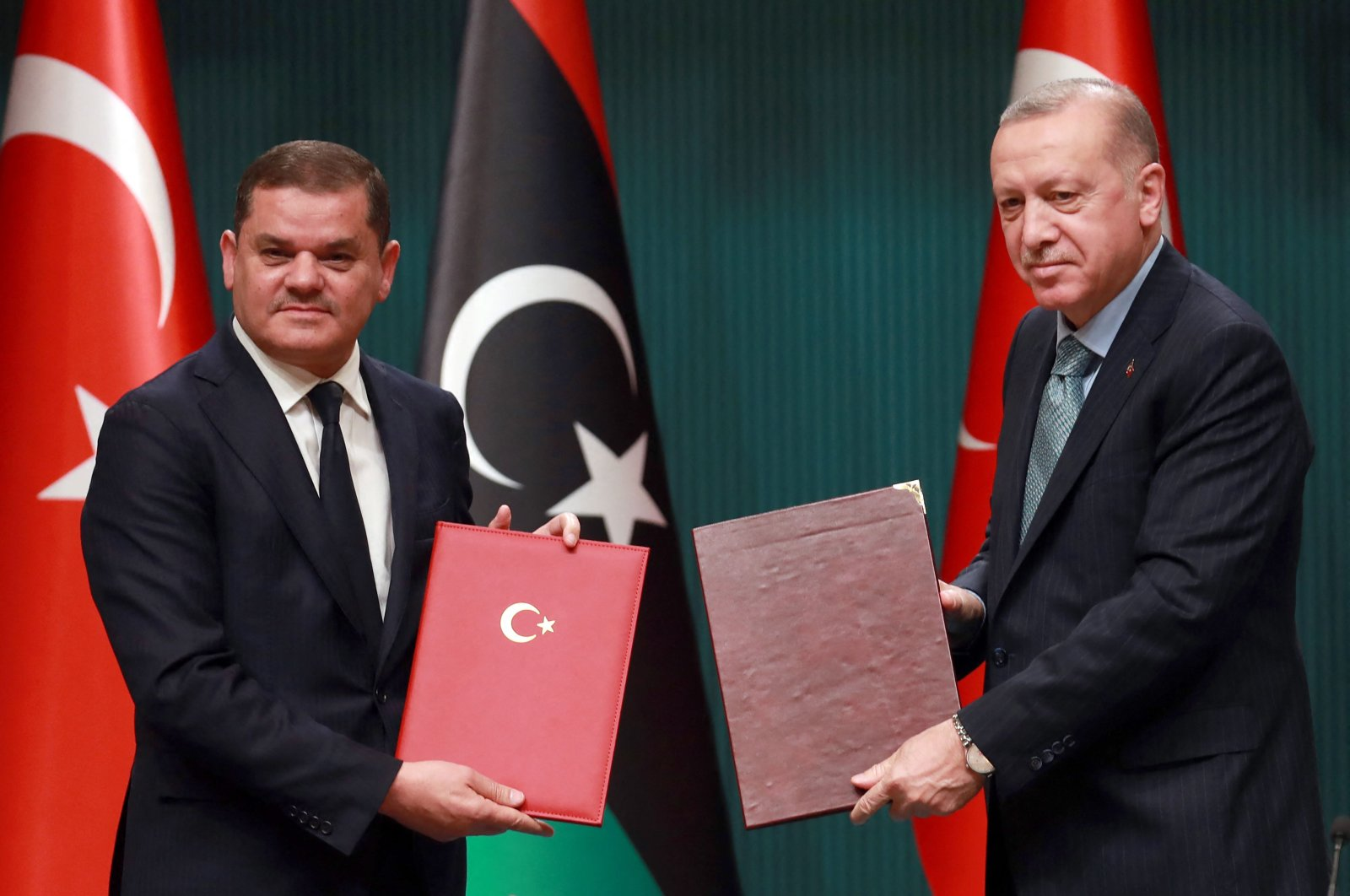 Turkish President Recep Tayyip Erdoğan (R) and Libya's interim Prime Minister Abdul Hamid Dbeibah pose for a photo during a signing ceremony after their meeting at the Presidential Palace in Ankara, Turkey, April 12, 2021. (Adem ALTAN/AFP Photo)