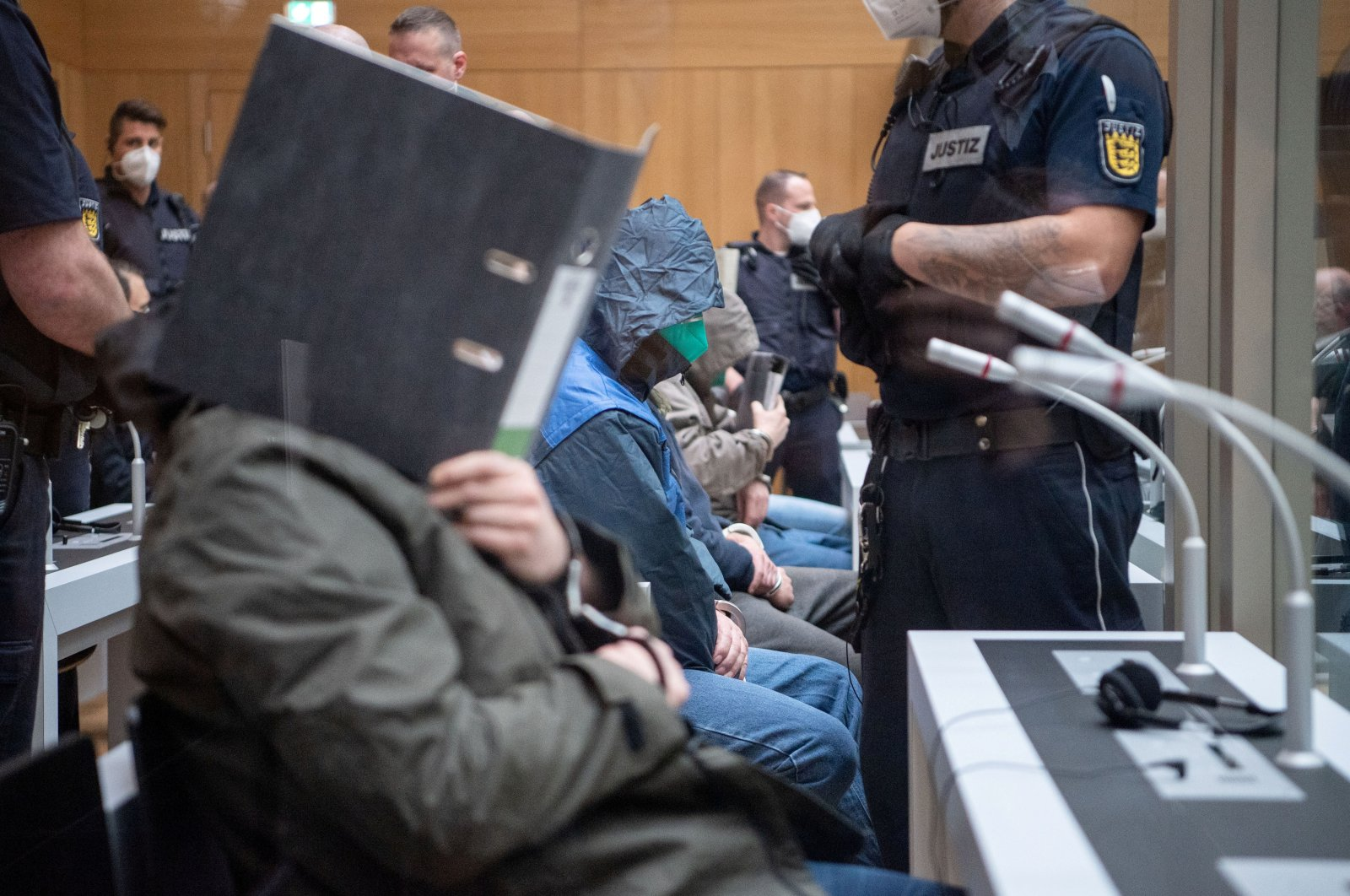 A defendant covers his face at the beginning of a trial against 11 Germans charged with belonging to a far-right organization, that prosecutors say aimed to attack mosques, at a higher regional court in Stuttgart, Germany, April 13, 2021. (Reuters Photo)