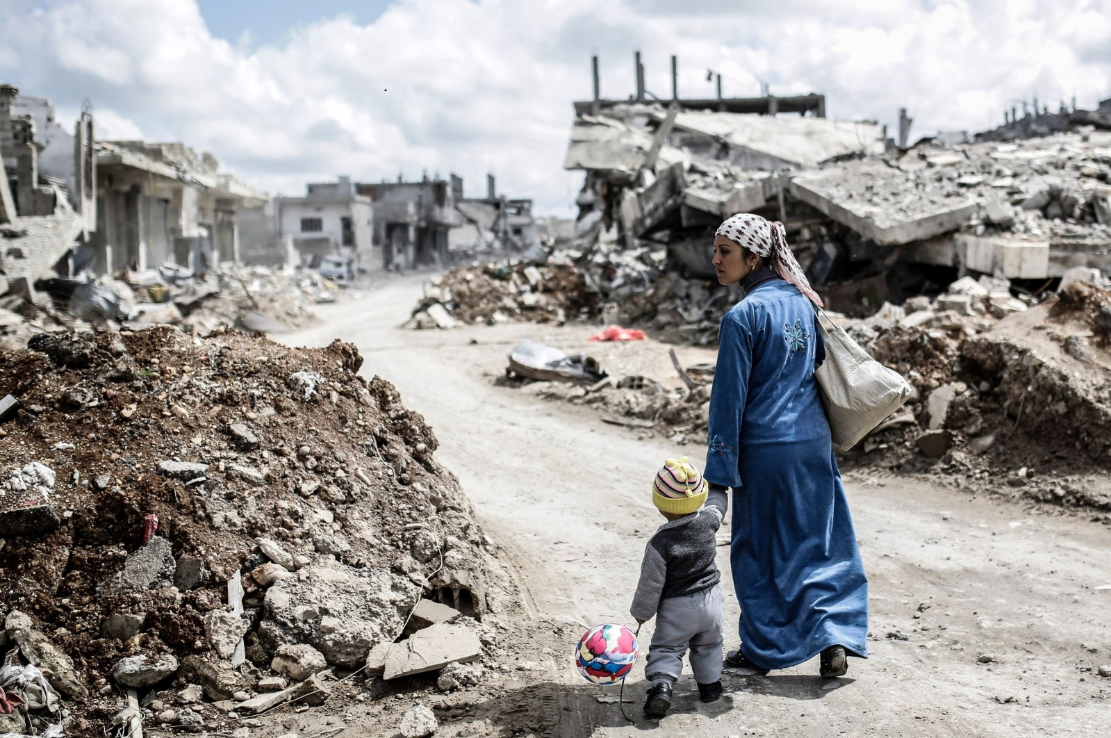 A Kurdish Syrian woman walks with her child past the ruins of the town of Kobane, also known as Ain al-Arab, Syria, March 25, 2015. (Yasin Akgul/AFP Photo)