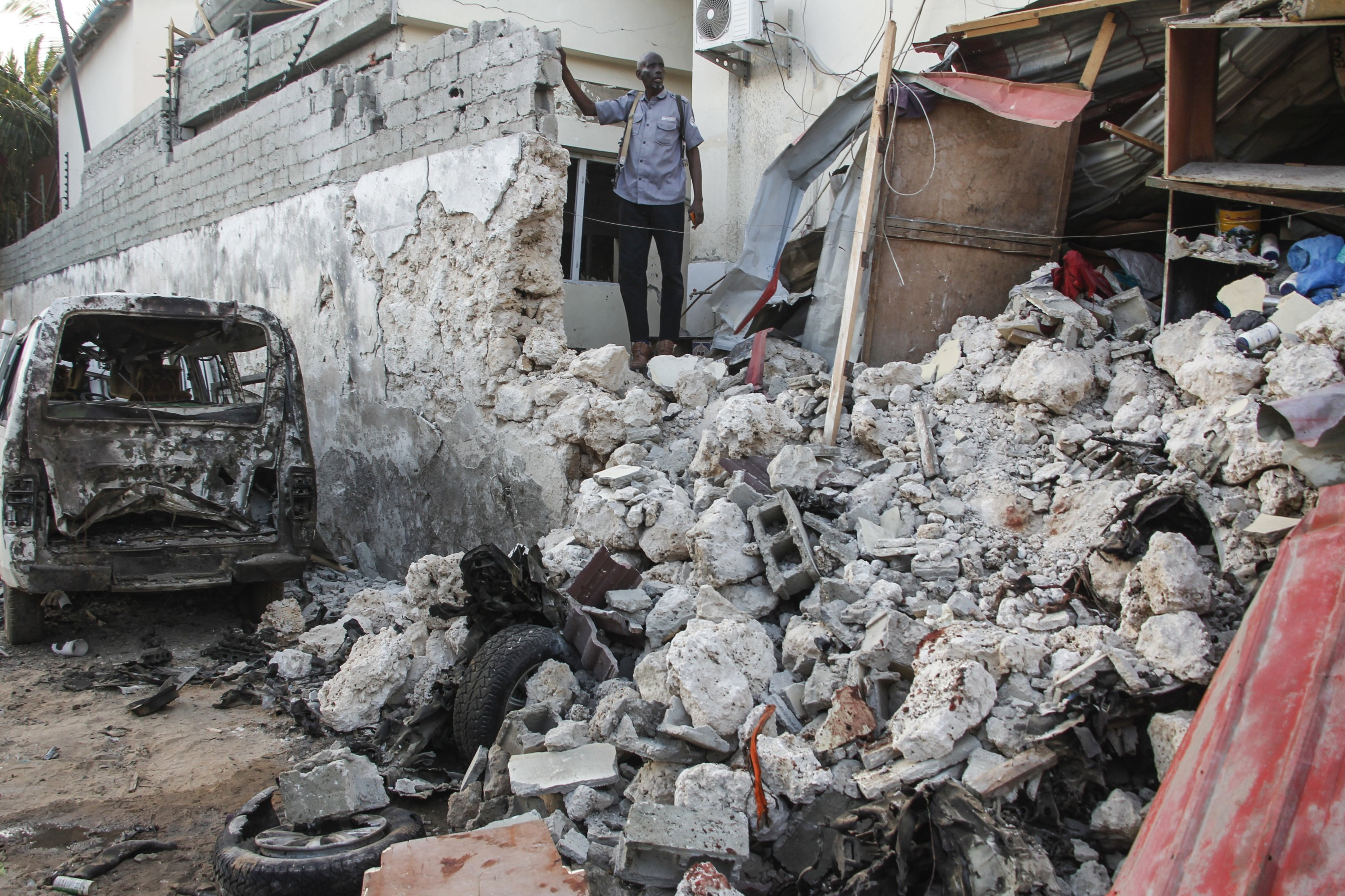 A hotel security guard stands by wreckage in the aftermath of an attack by the al-Shabab terrorist group on the Afrik hotel in Mogadishu, Somalia, Feb. 1, 2021. (AP Photo)