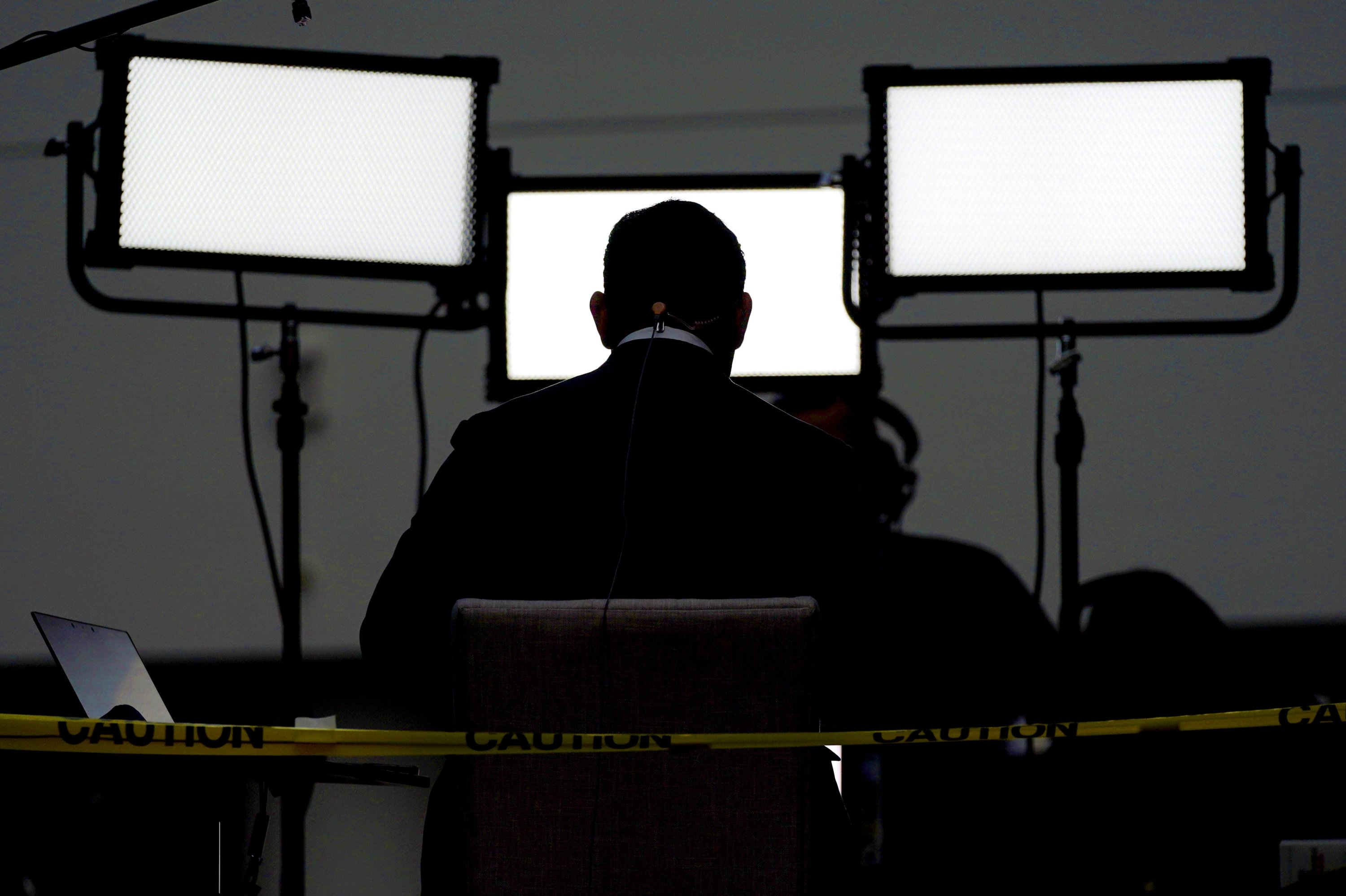A broadcast journalist sits in front of lights ahead of the first presidential debate between Republican candidate President Donald Trump and Democratic candidate former Vice President Joe Biden at the Health Education Campus of Case Western Reserve University, Cleveland, Ohio, the U.S., Sept. 29, 2020. (AP Photo)