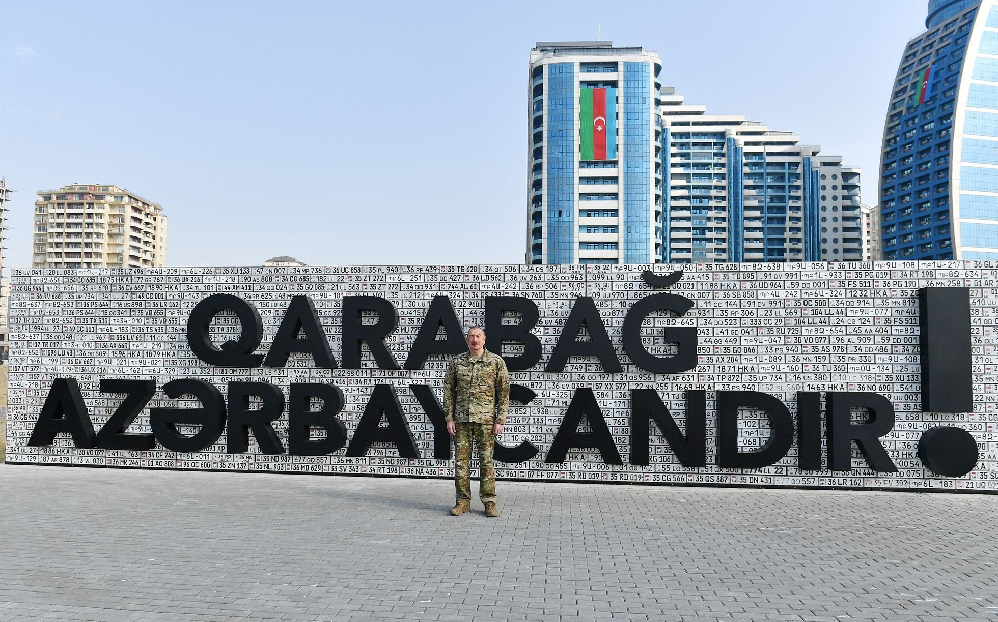 Azerbaijani President Ilham Aliyev stands in front of a wall decorated with Armenian license plates and reading 'Karabakh is Azerbaijan!' as he tours the open-air museum that showcases military equipment seized from Armenian troops during the Nagorno-Karabakh war last year, Baku, Azerbaijan, April 12, 2021 (Handout photo from the Azerbaijani Presidential Press Office via AFP).
