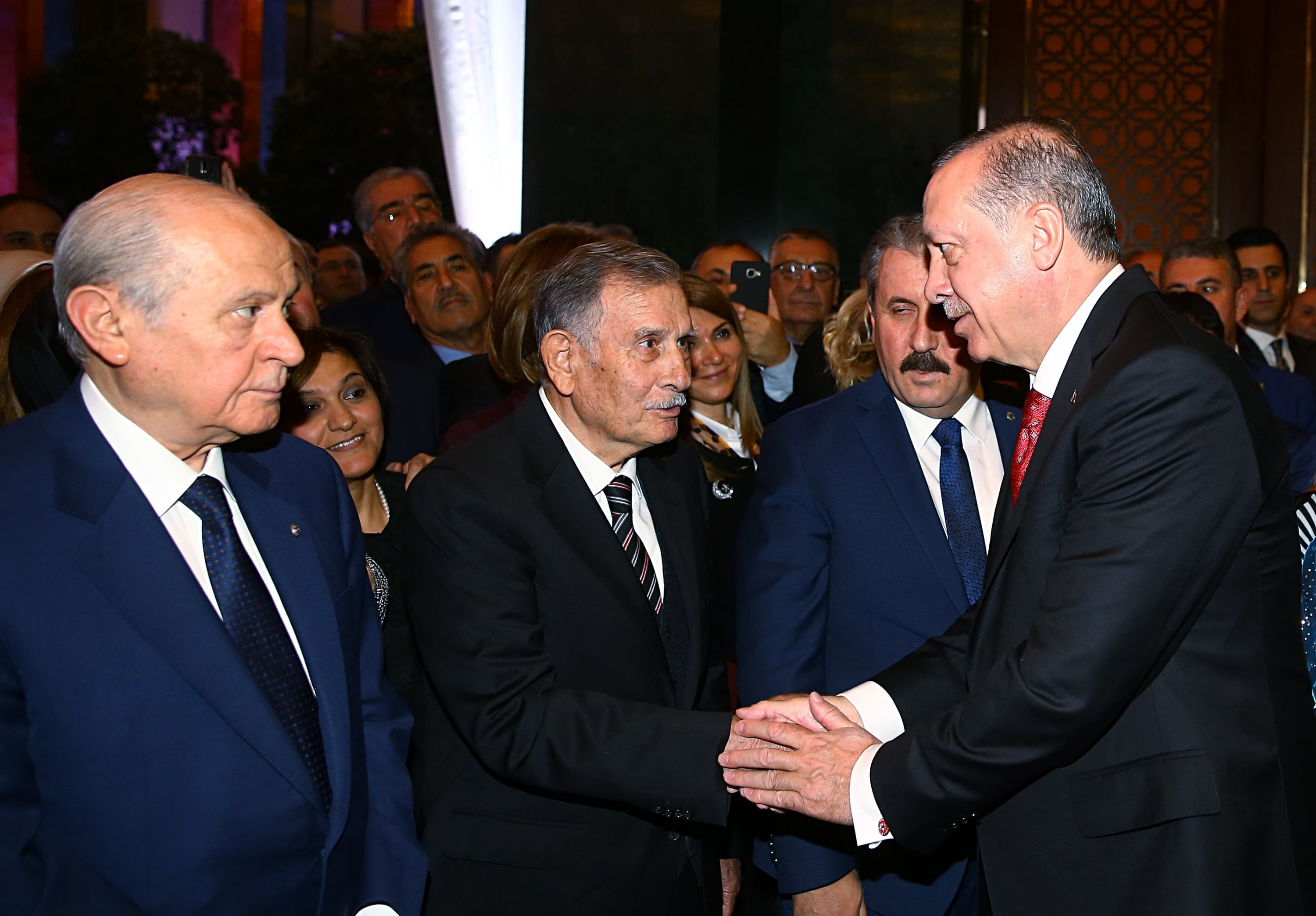 President Recep Tayyip Erdoğan (R) shakes hands with Presidential High Advisory Board (YİK) member and former Parliament Speaker and Prime Minister Yıldırım Akbulut (2nd L), alongside MHP leader Devlet Bahçeli (L) and BBP chair Mustafa Destici, during the reception held to mark Oct 27, 2017 Republic Day, in the capital Ankara, Turkey, in this image provided on April 14, 2021. (AA Photo).