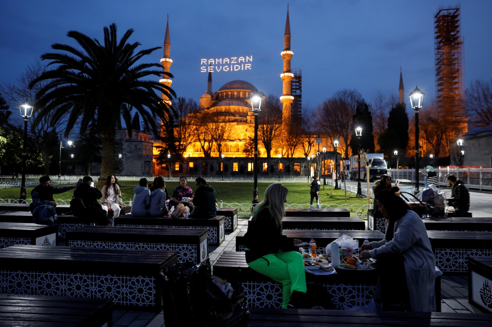 Muslims eat their iftar meals in front of Sultanahmet Mosque (Blue Mosque) in Istanbul, Turkey, April 13, 2021. (REUTERS PHOTO)